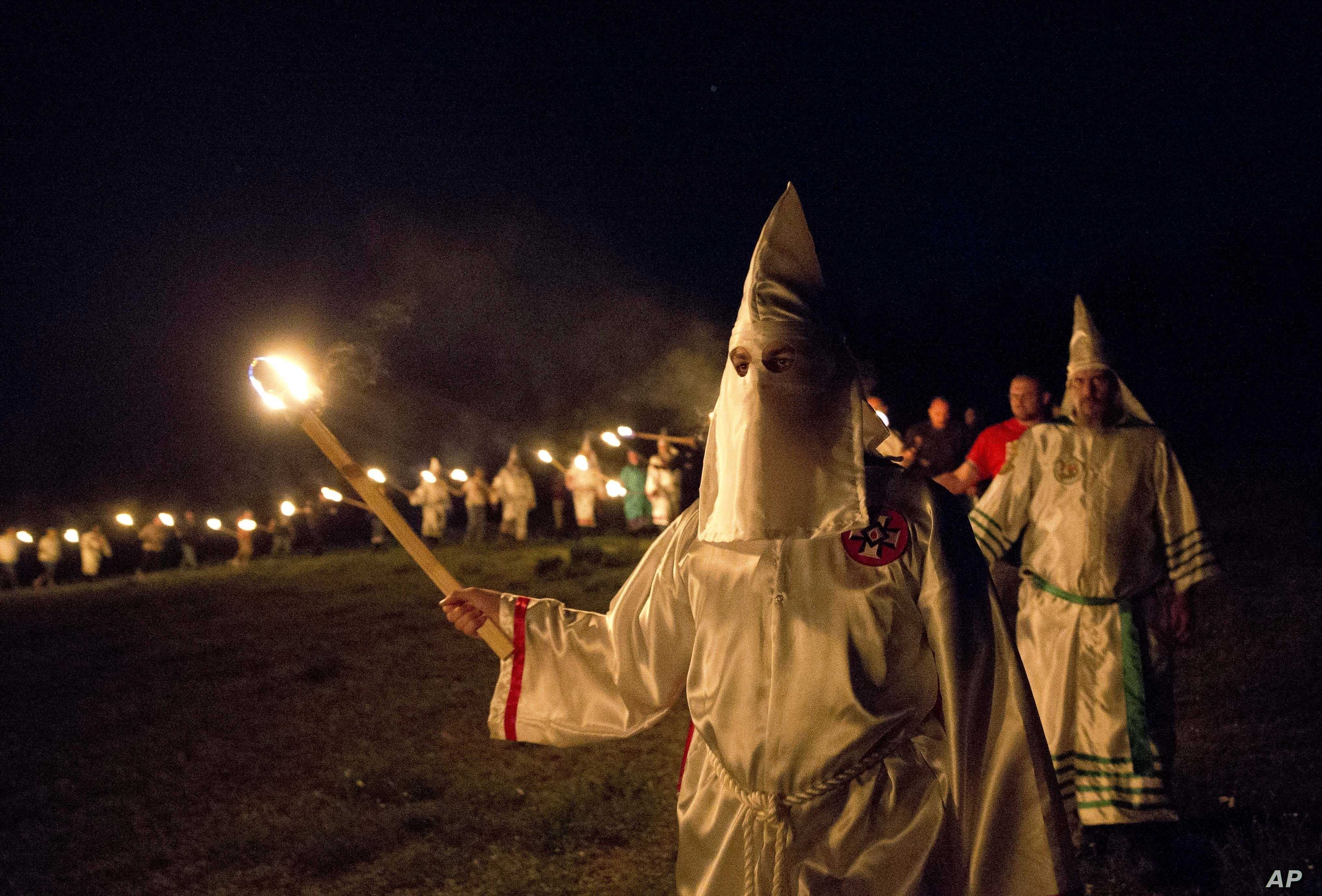"""In this Saturday, April 23, 2016 photo, members of the Ku Klux Klan participate in cross burnings after a """"white pride"""" rally in rural Paulding County near Cedar Town, Ga. Born in the ashes of the smoldering South after the Civil War, the KKK died an..."""