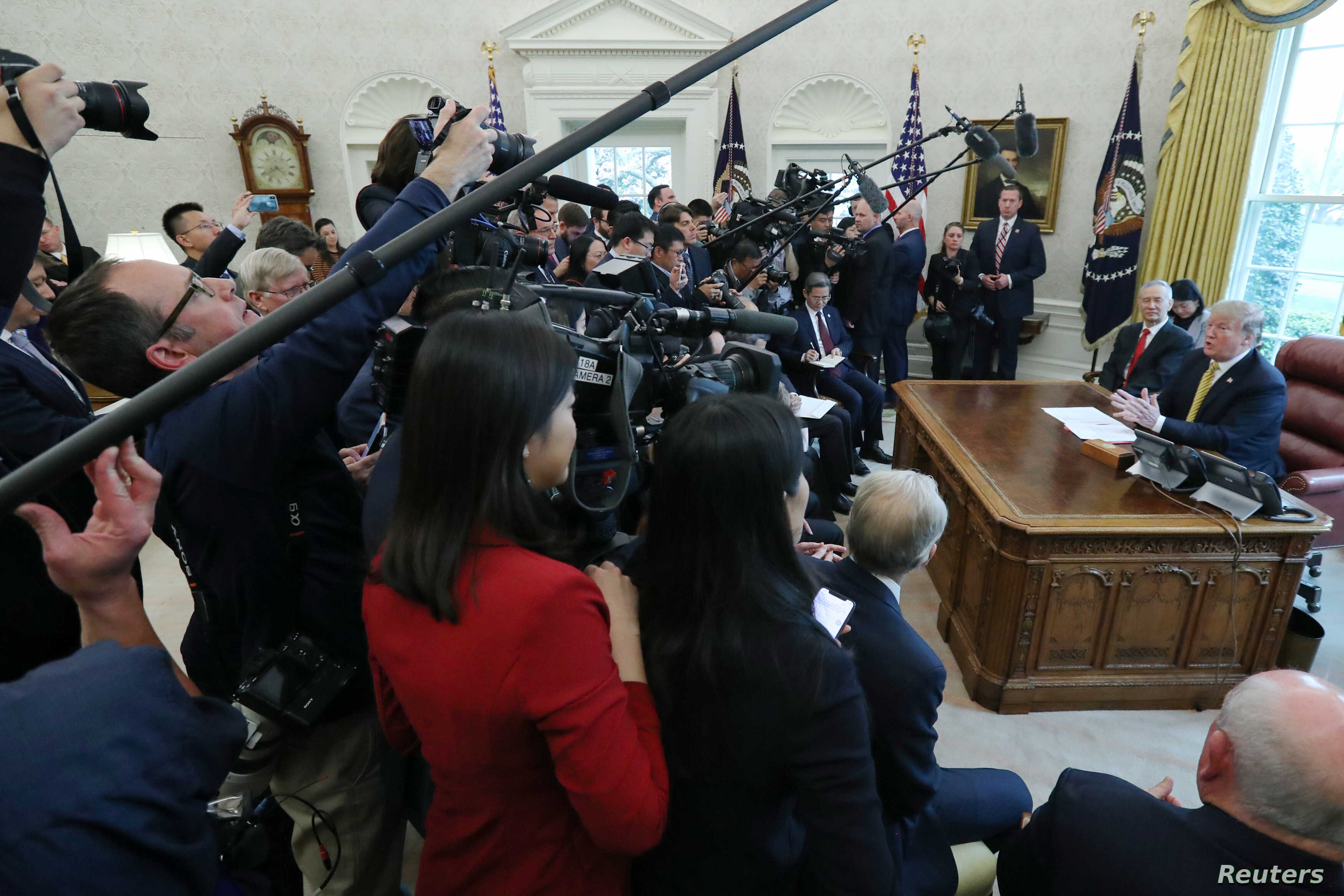 Surrounded by the press, President Donald Trump speaks while meeting with China's Vice Premier Liu He in the Oval Office of the White House in Washington,  April 4, 2019.