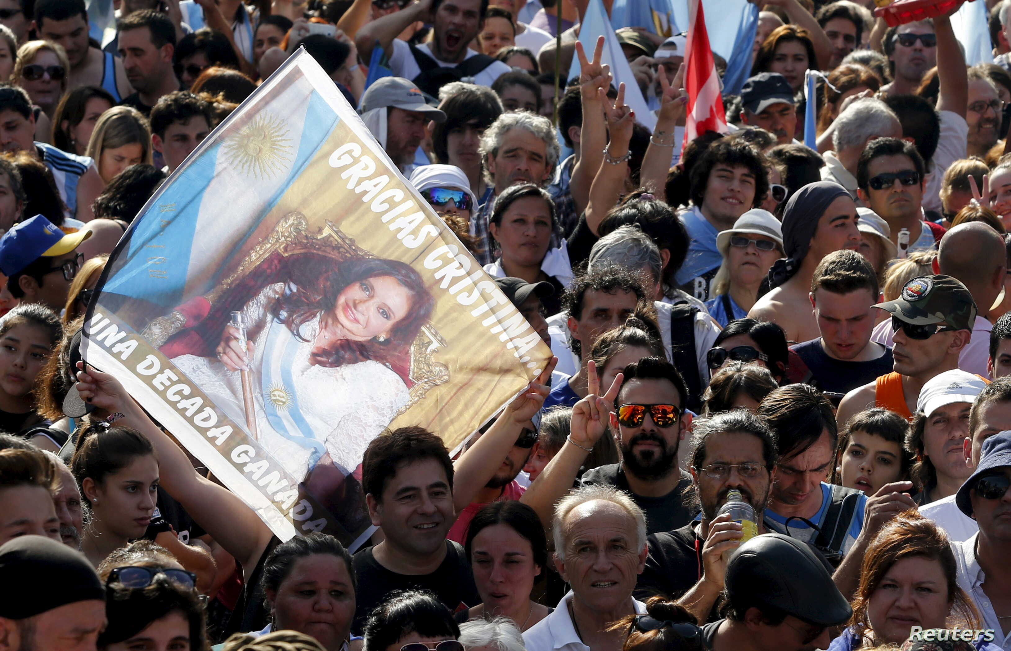 "People wait for the speech of Argentina's President Cristina Fernandez de Kirchner while carrying a banner that reads ""Gracias Cristina"" during a rally in front of the Casa Rosada Presidential Palace in Buenos Aires, Argentina, Dec. 9, 2015."