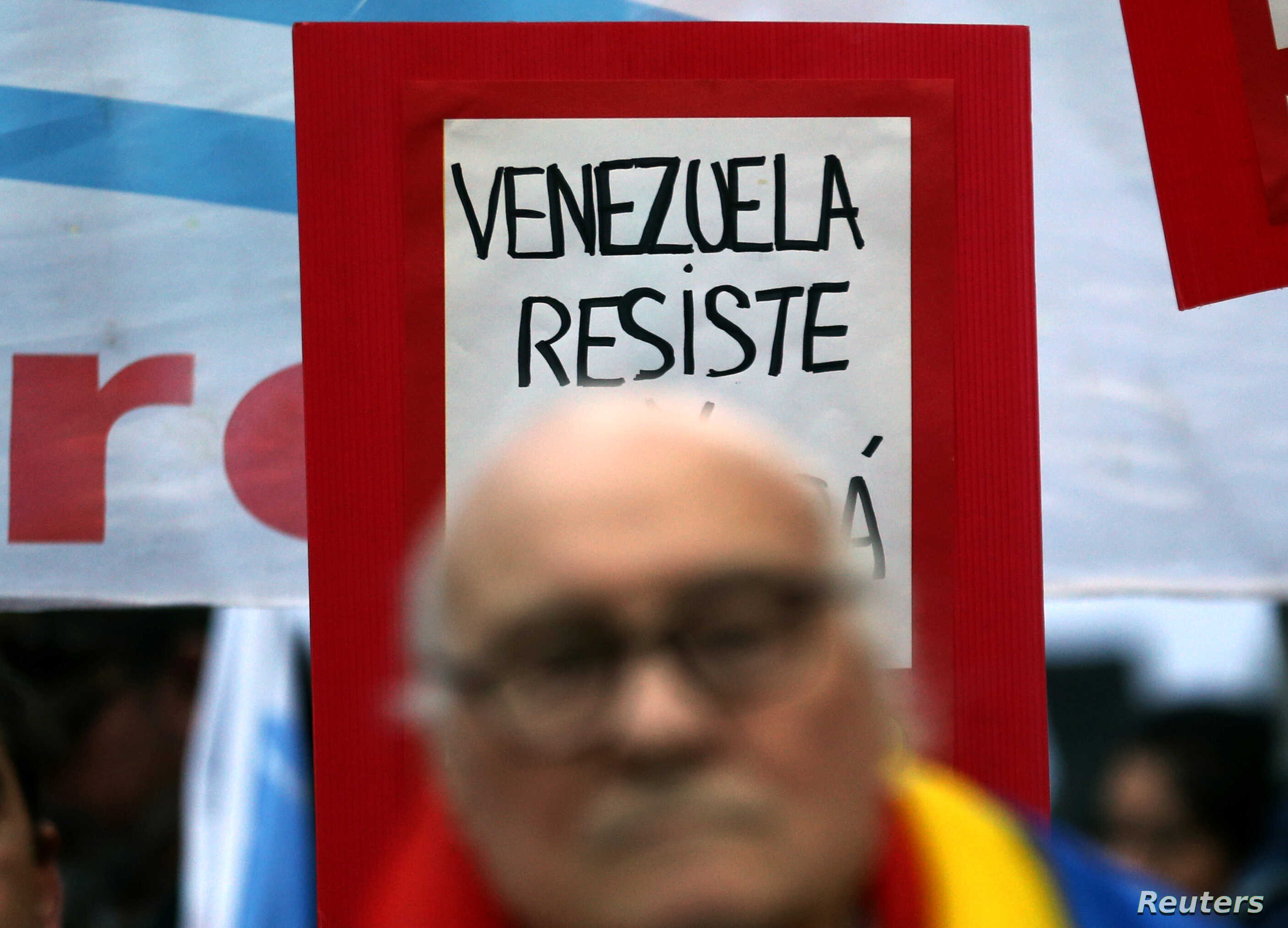 """A sign that reads """"Venezuela, resist"""" is seen behind former Argentine leftist guerrilla leader Roberto Perdia during a protest in support of Venezuela's government in Buenos Aires, Argentina, Aug. 17, 2017."""