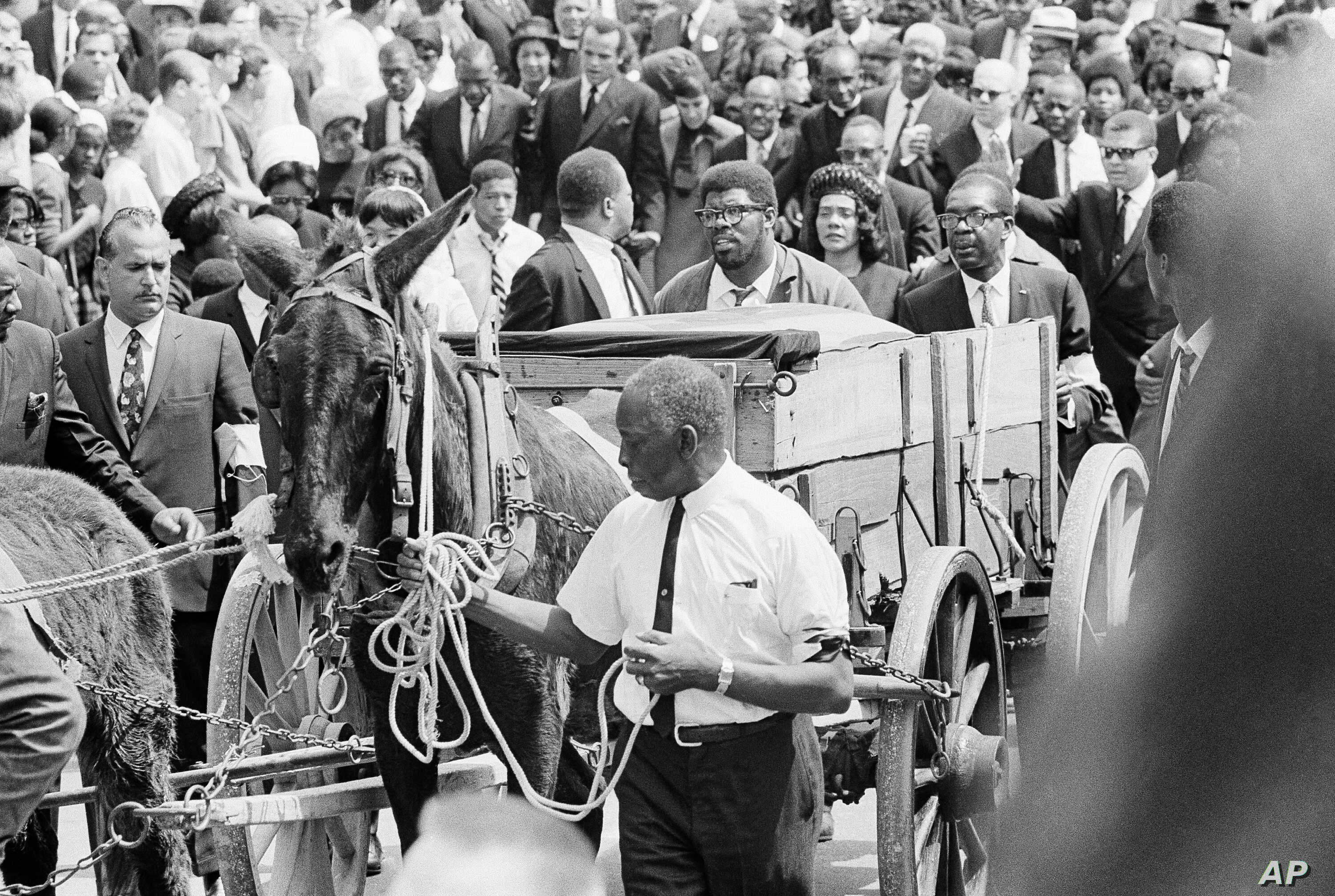 FILE - A mule cart carries Martin Luther King Jr.'s mahogany casket through the streets of Atlanta, April 10, 1968, en route to funeral services at Morehouse College.