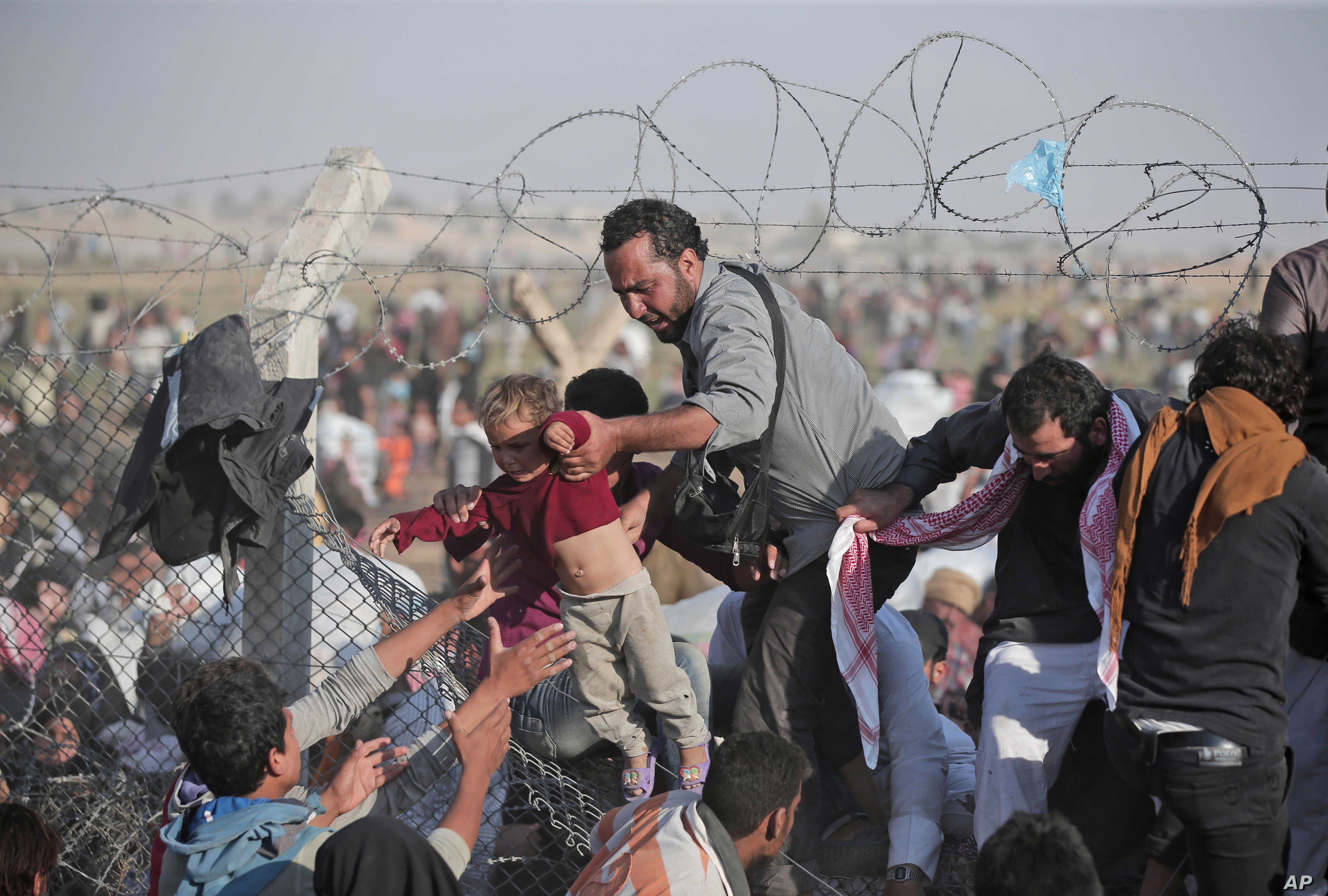 FILE - A Syrian refugee hands a toddler over a broken border fence into Turkey in Akcakale, Sanliurfa province, southeastern Turkey, June 14, 2015.