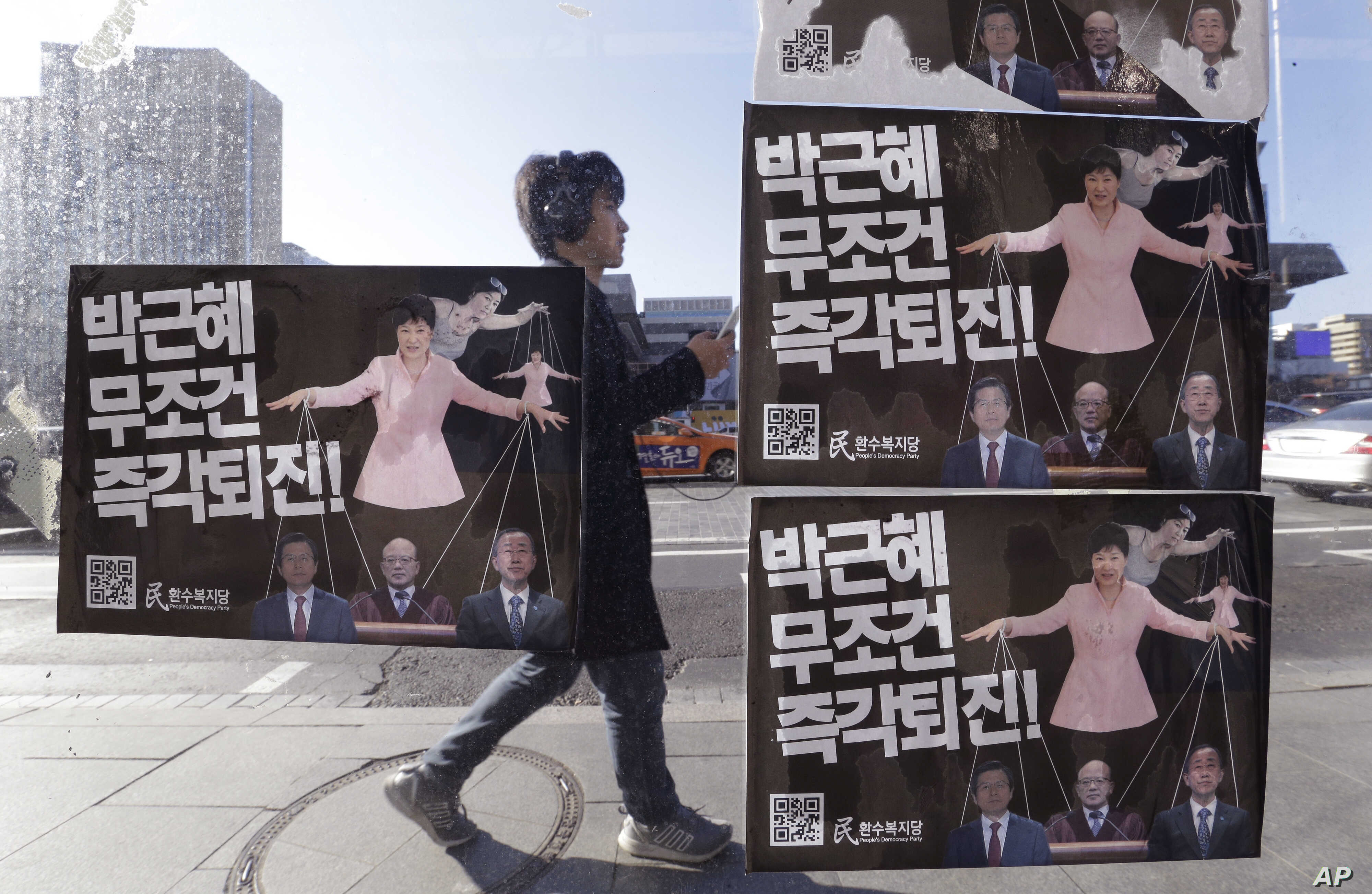 A man walks by a bus stop displayed with posters depicting impeached South Korea's President Park Geun-hye in pink manipulating three of her aides while she is also manipulated as a marionette by her jailed confidante Choi Soon-sil, seen above Park's...