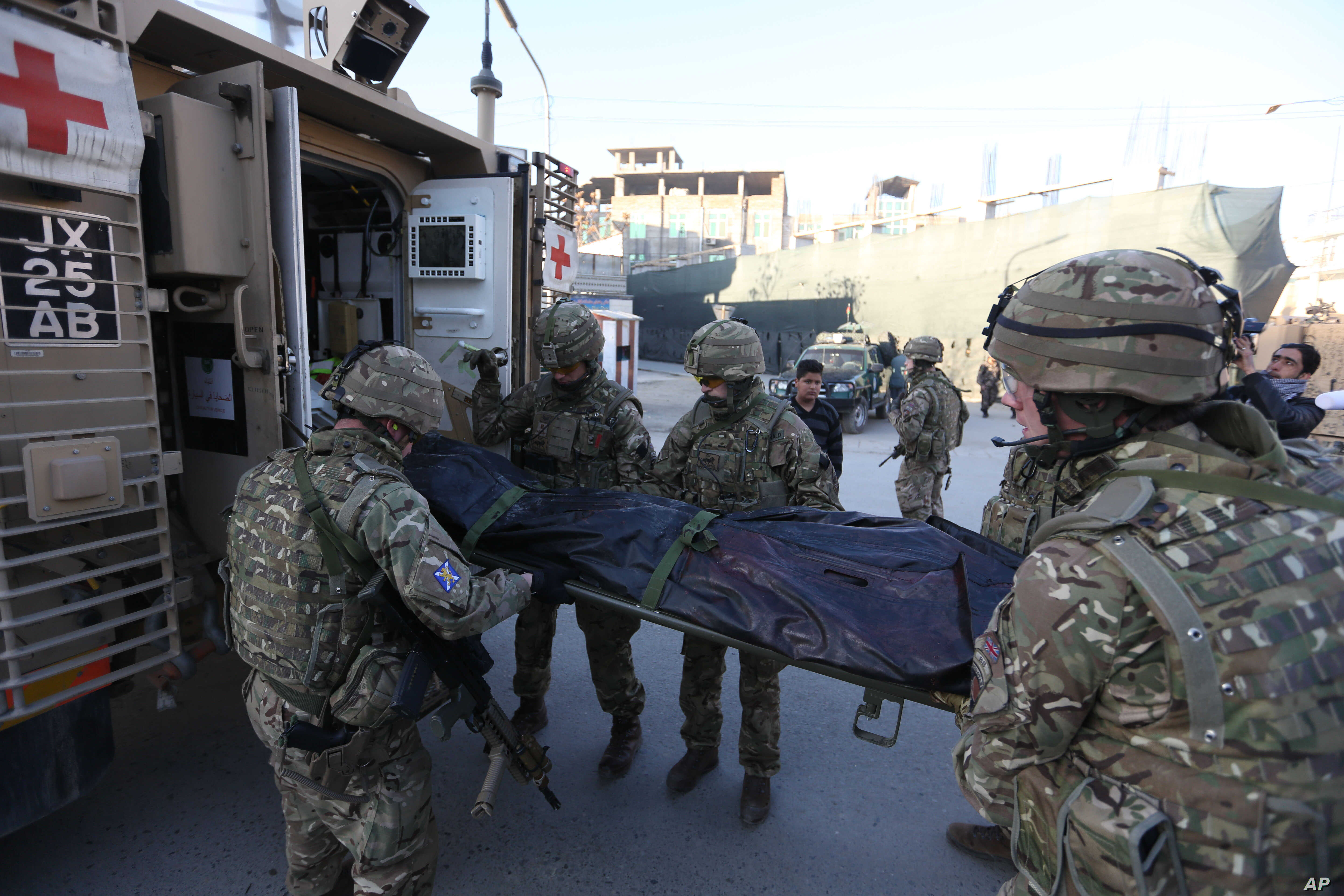 British soldiers carry the dead body of a victim in an attack near Spanish Embassy in Kabul, Afghanistan, Dec. 12, 2015.