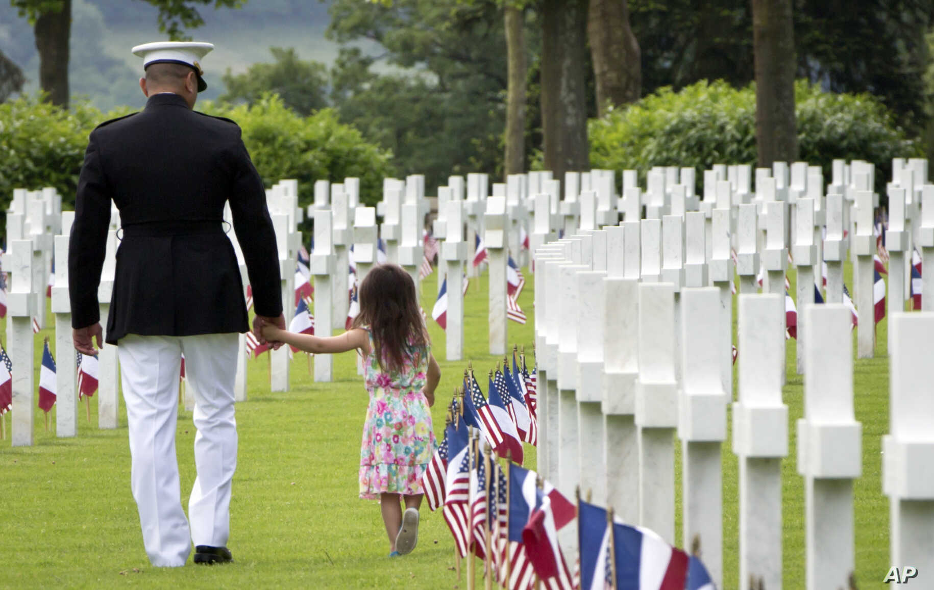 A U.S. Marine Corps soldier holds hands with a small girl as they walk among headstones of World War I dead at a Memorial Day commemoration at the Aisne-Marne American Cemetery in Belleau, France, May 27, 2018.