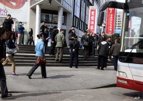 Plainclothes security personnel film as they gather to load detained worshippers onto a waiting bus near a building that leaders of the unregistered Shouwang house church had told parishioners to gather in Beijing, China, April 10, 2011