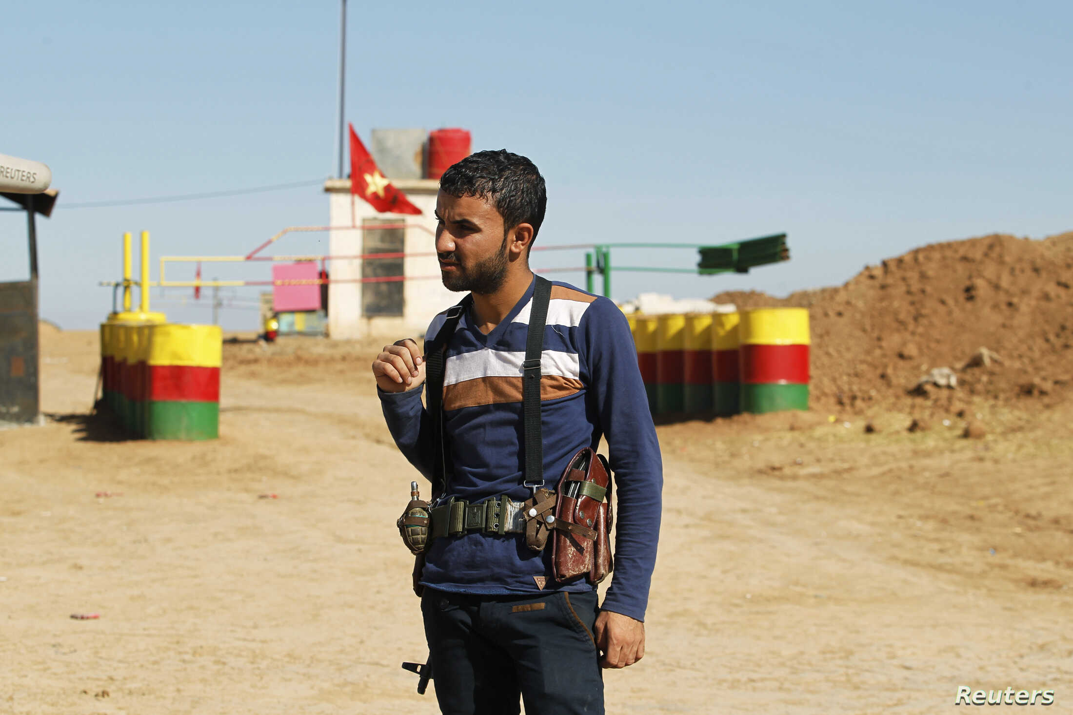 FILE - An officer of the Syrian Kurdish Democratic Union Party (PYD) stands guard near the Syrian-Iraq border.