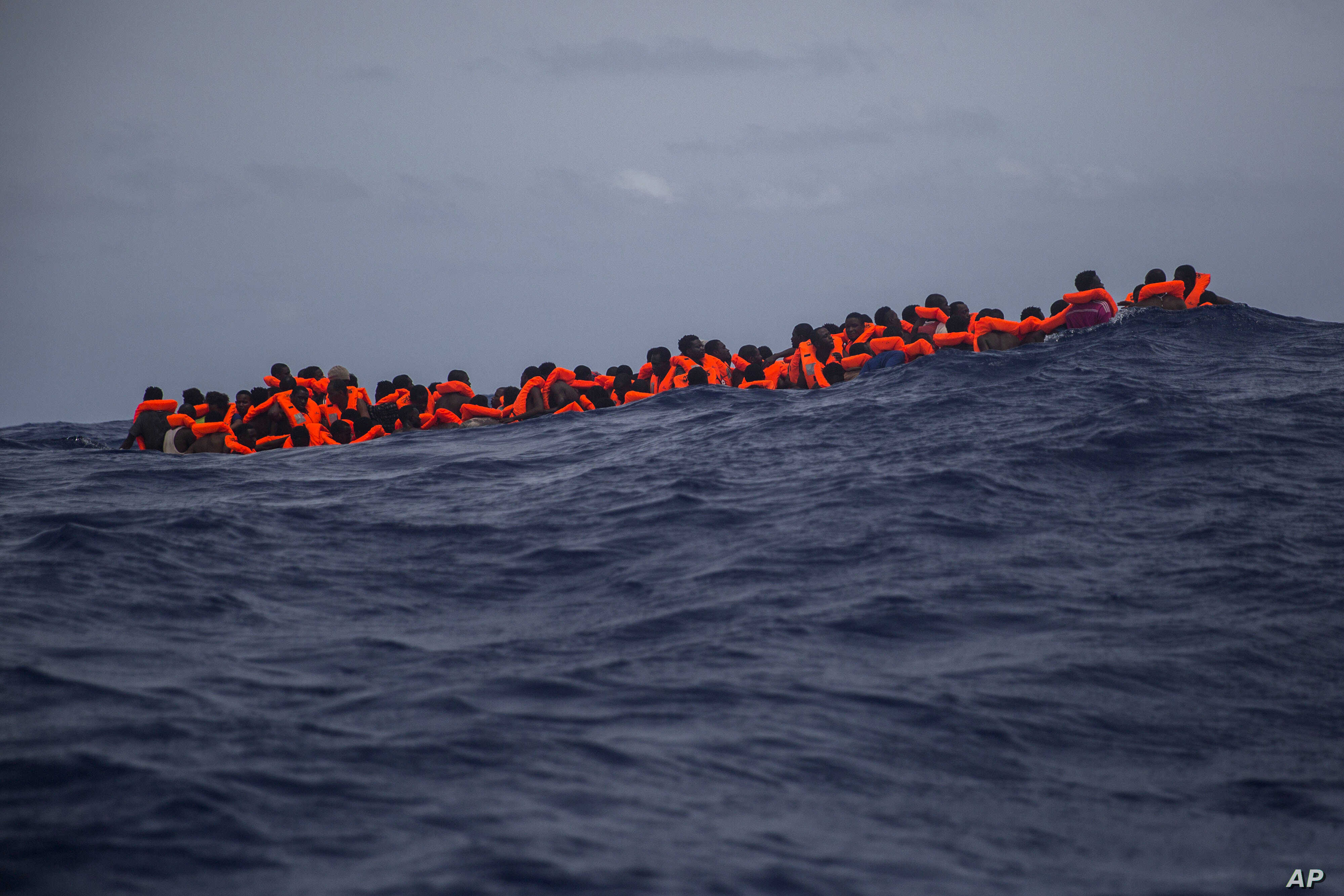 Migrants wait to be rescued by aid workers of Spanish NGO Proactiva Open Arms in the Mediterranean Sea, about 15 miles north of Sabratha, Libya on July 25, 2017. More than 120 migrants were rescued Tuesday from the Mediterranean Sea while many — in...