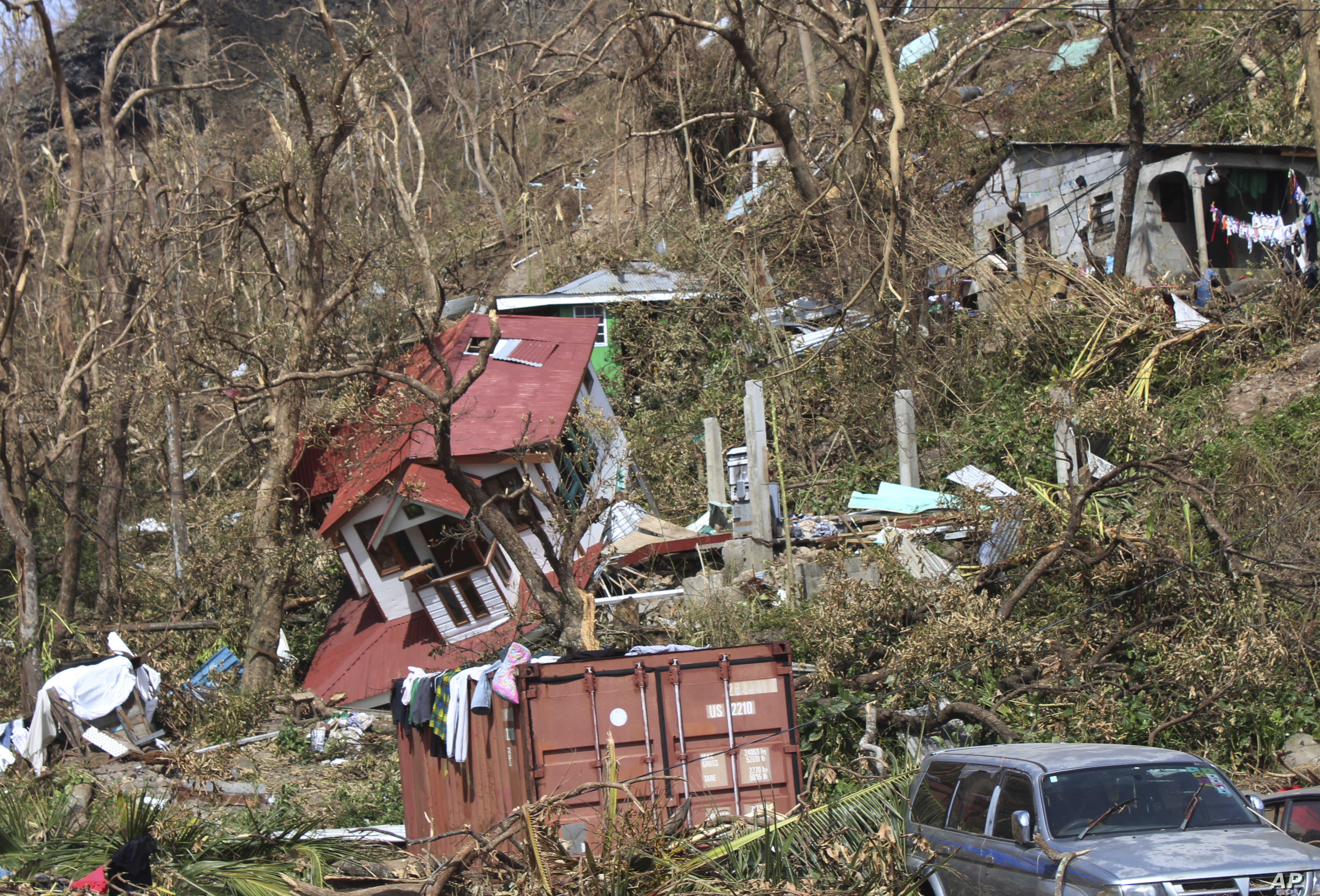 FILE - In this Sept. 23, 2017, photo, homes lay scattered after the passing of Hurricane Maria in Roseau, the capital of the island of Dominica.