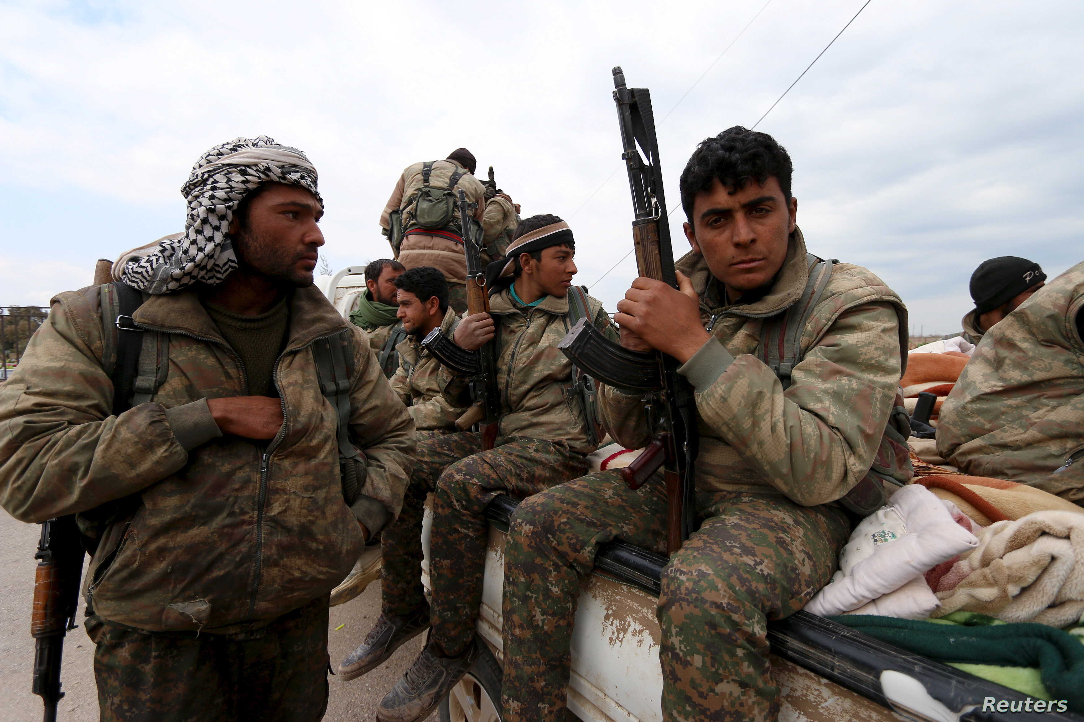 Kurdish People's Protection Units (YPG) fighters carry their weapons while riding on the back of a pick-up truck in Qamishli, Syria, March 11, 2016.