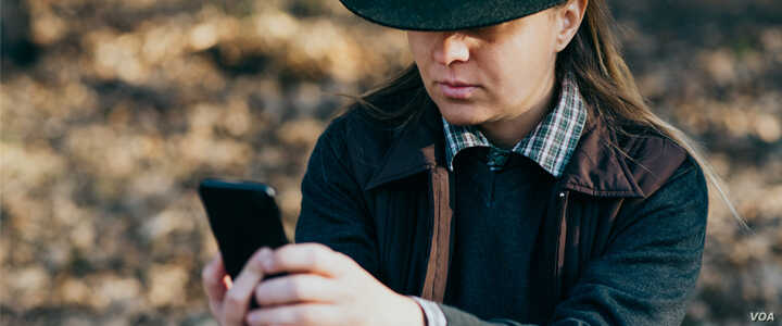 Photo shows unidentified Native American tribe member holding a cell phone. Courtesy, U.S. Department of Health and Human Services.