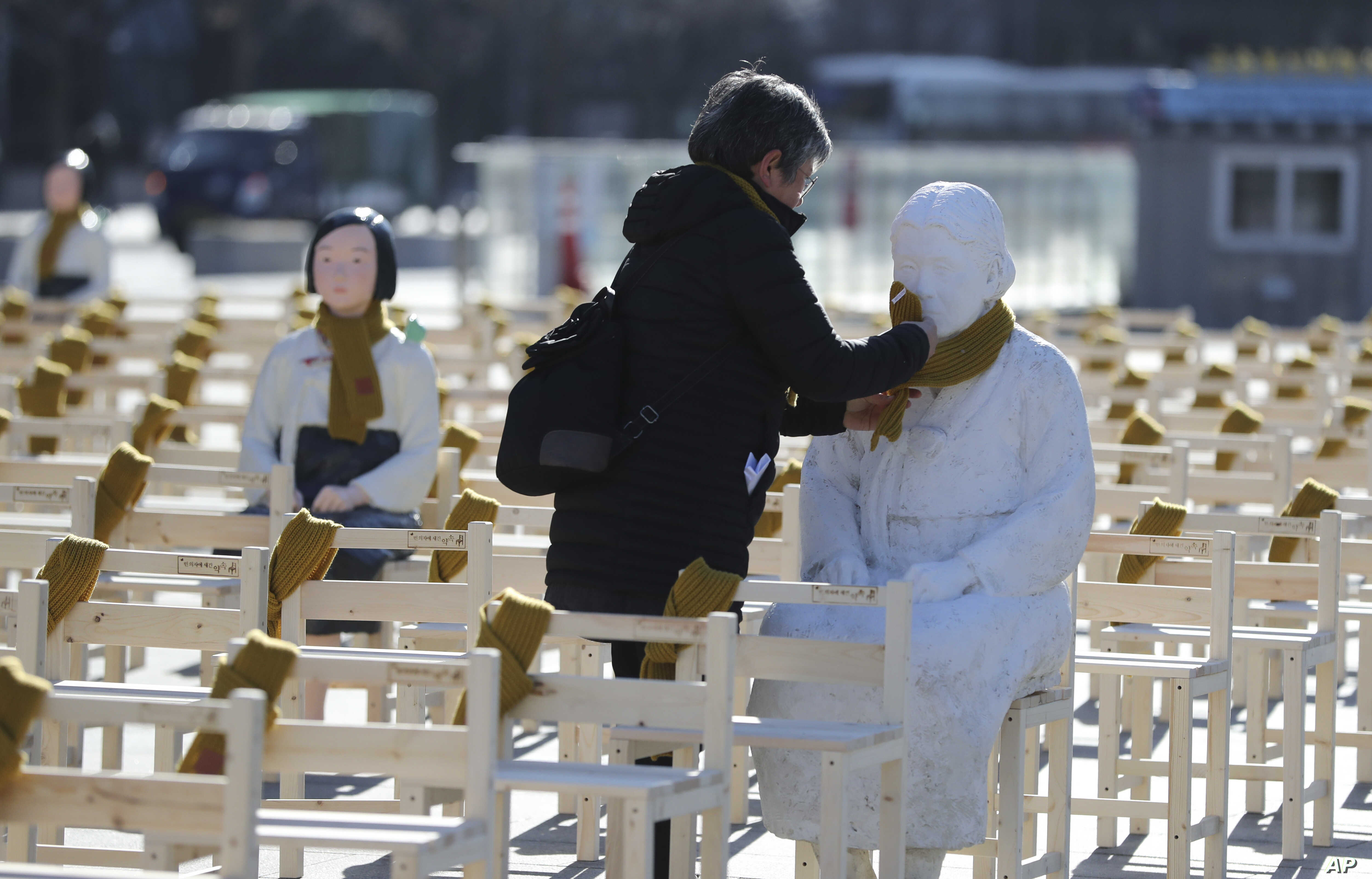 A woman puts a scarf on a statue of a comfort woman sitting in a installation of empty chairs symbolizing the victims in Seoul, South Korea, Dec. 27, 2017.
