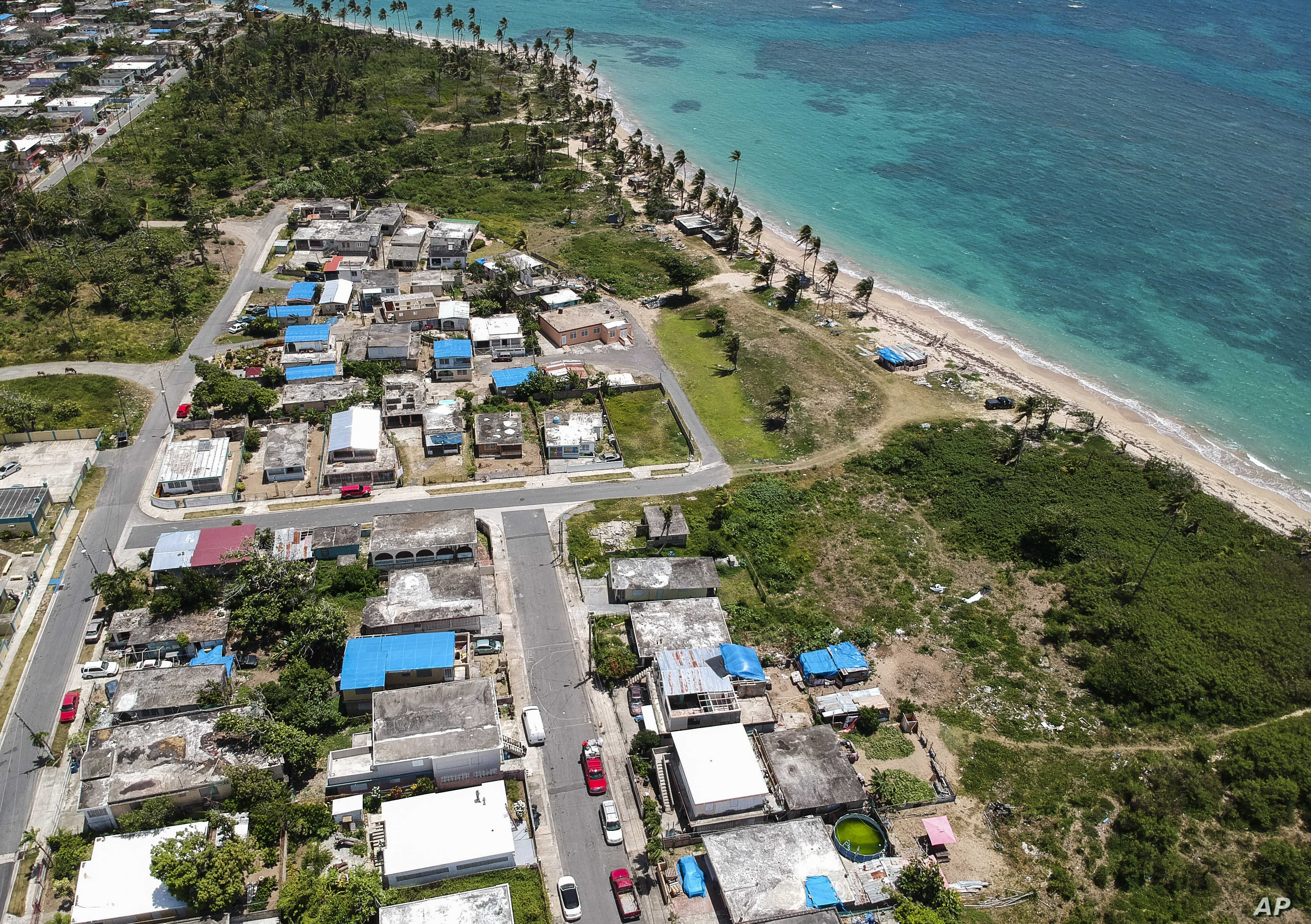 FILE - This June 18, 2018 file photo shows an aerial photo of the Viequez neighborhood, east of San Juan, Puerto Rico, where people were still living in damaged homes, protected by blue plastic tarps, months since Hurricane Maria devastated the islan