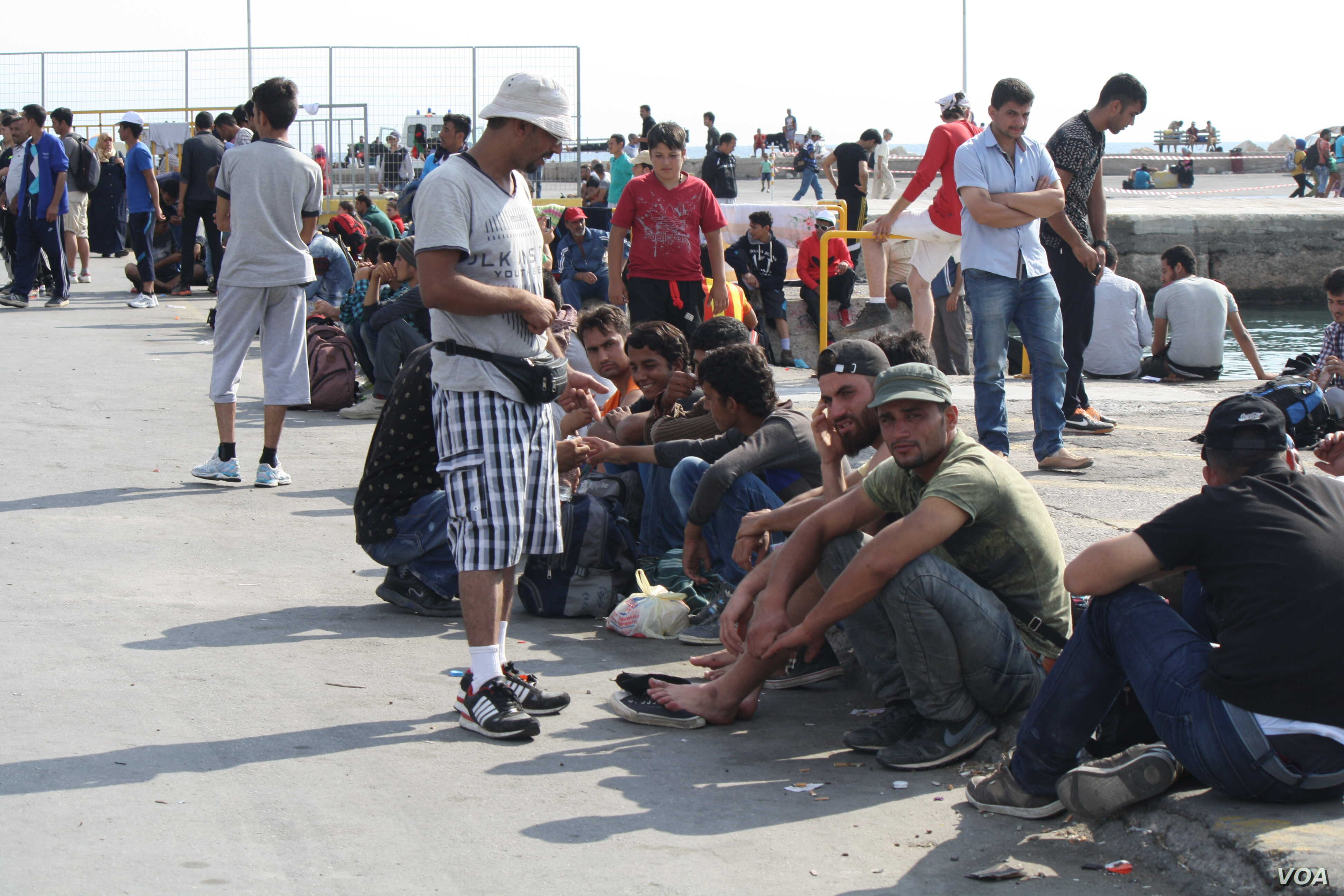 As the passengers loaded, those who could not get a ticket wait on the streets, hoping to board in the coming days, Sept. 12, 2015. (Credit: Heather Murdock/VOA)