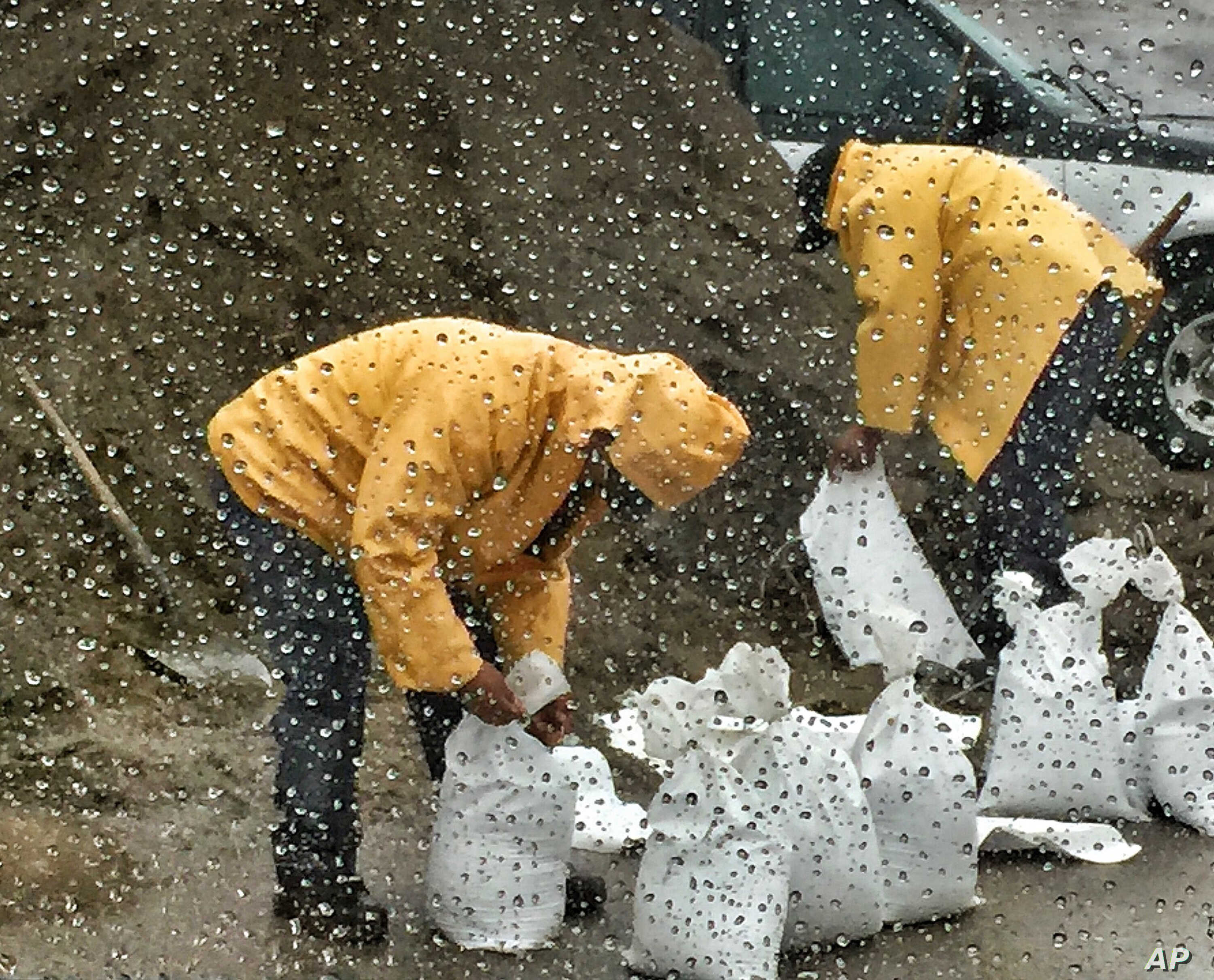 In this photo taken through a glass window, released by Santa Barbara County Fire Department, people fill up sandbags under the rain in Santa Barbara, California, Jan. 8, 2018.