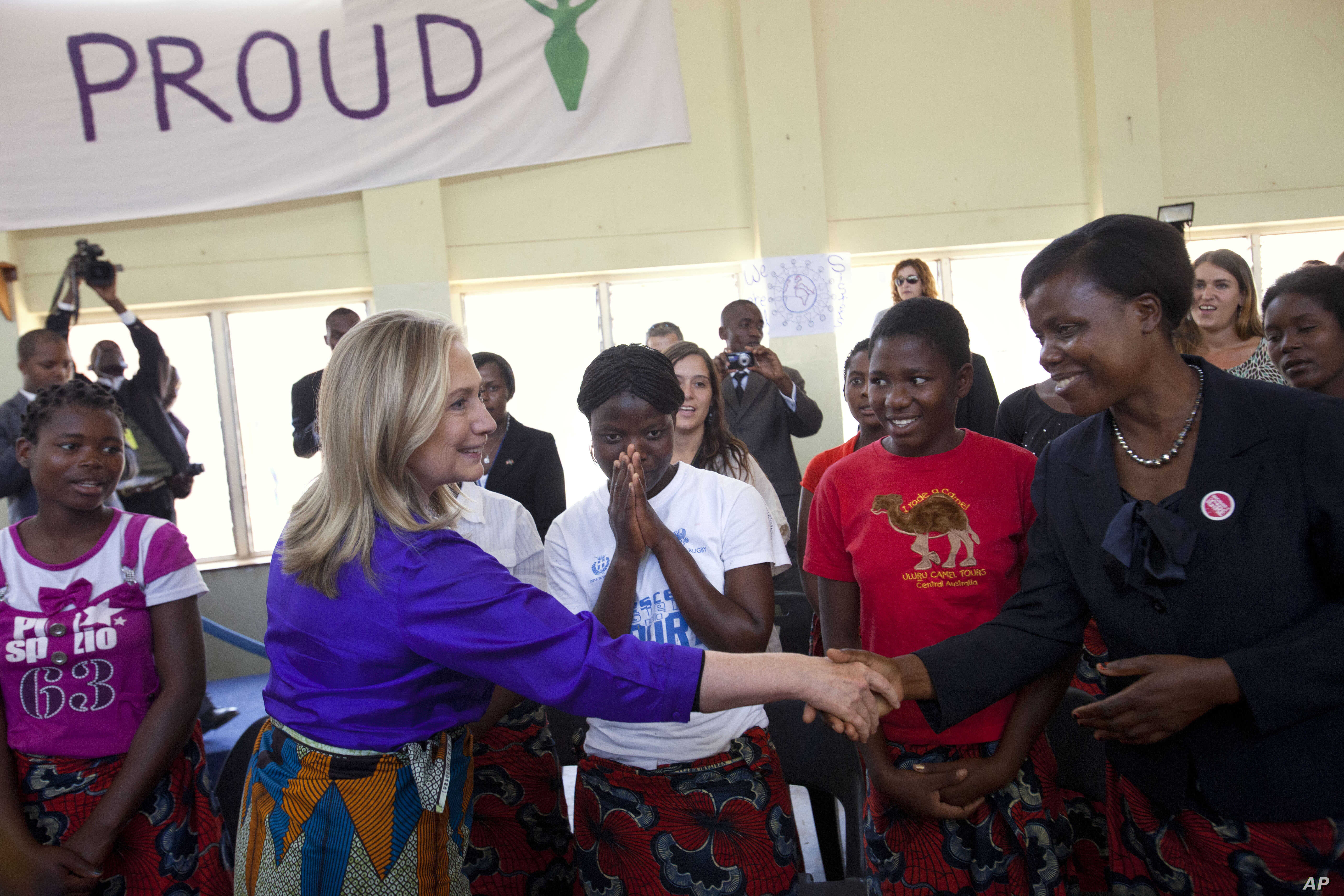 Girls react as U.S. Secretary of State Hillary Rodham Clinton shakes hands at Camp GLOW (Girls Leading Our World) run by the Peace Corps, in Lilongwe, Malawi, Aug. 5, 2012.
