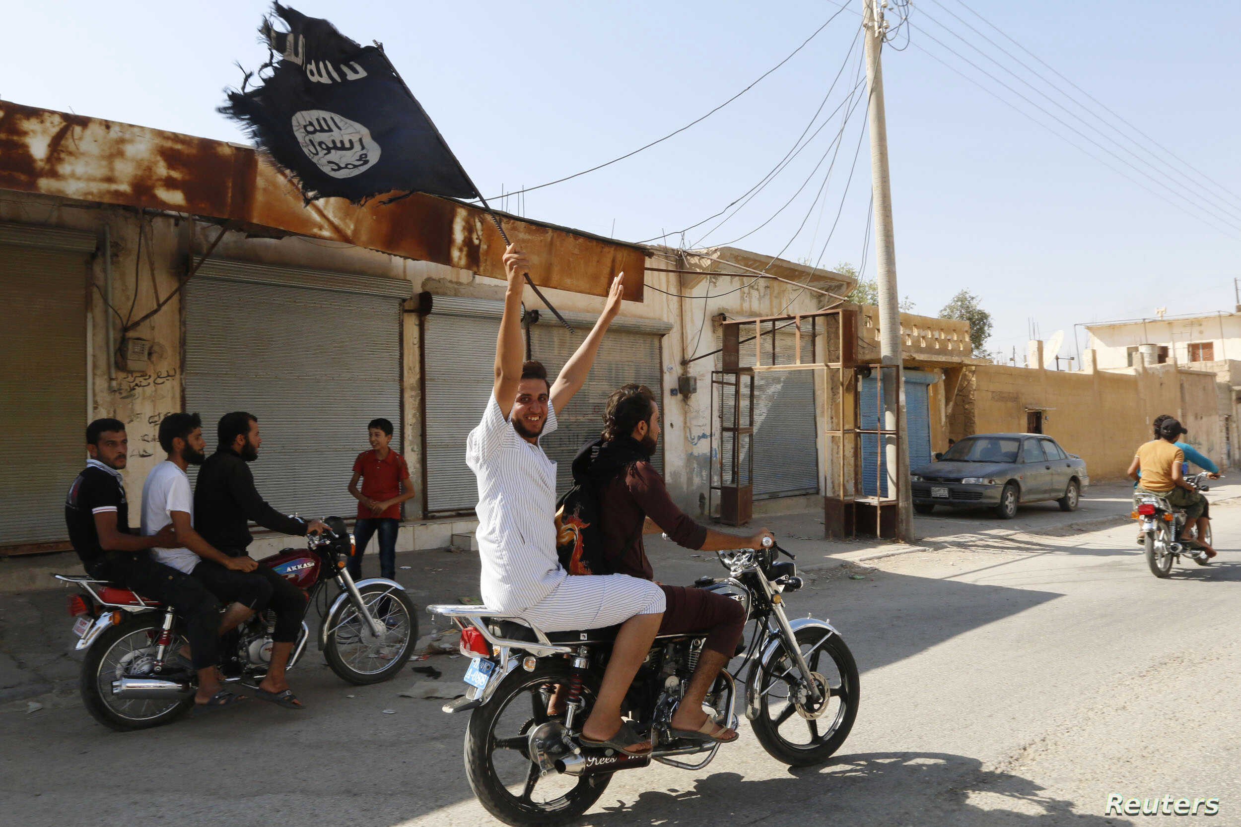 A resident of Tabqa city touring the streets on a motorcycle waves an Islamist flag in celebration after Islamic State militants took over Tabqa air base, in nearby Raqqa, Syria, Aug. 24, 2014.