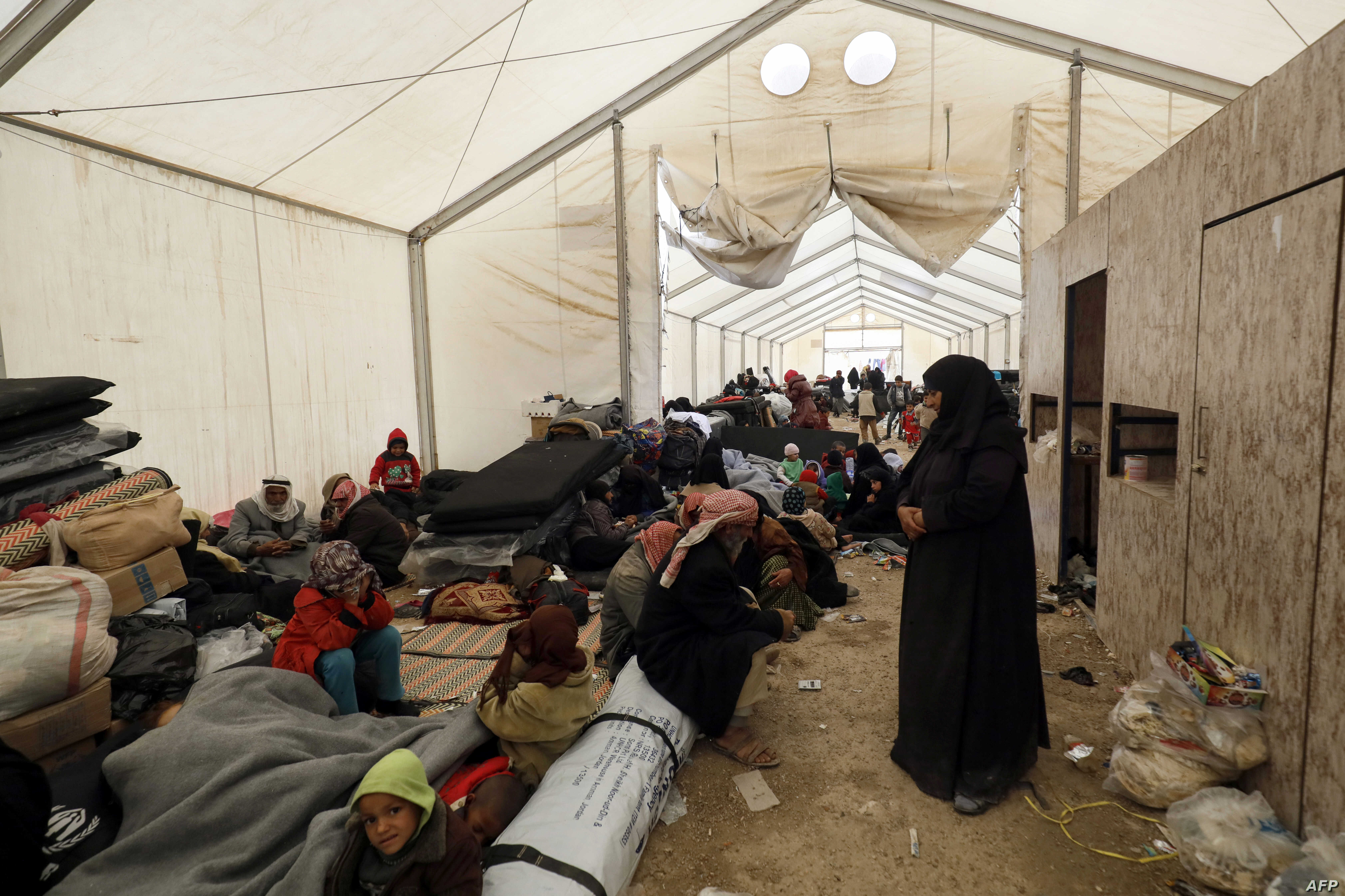 FILE - Displaced people gather inside a tent in the al-Hol camp in northeastern Syria, Dec. 8, 2018.