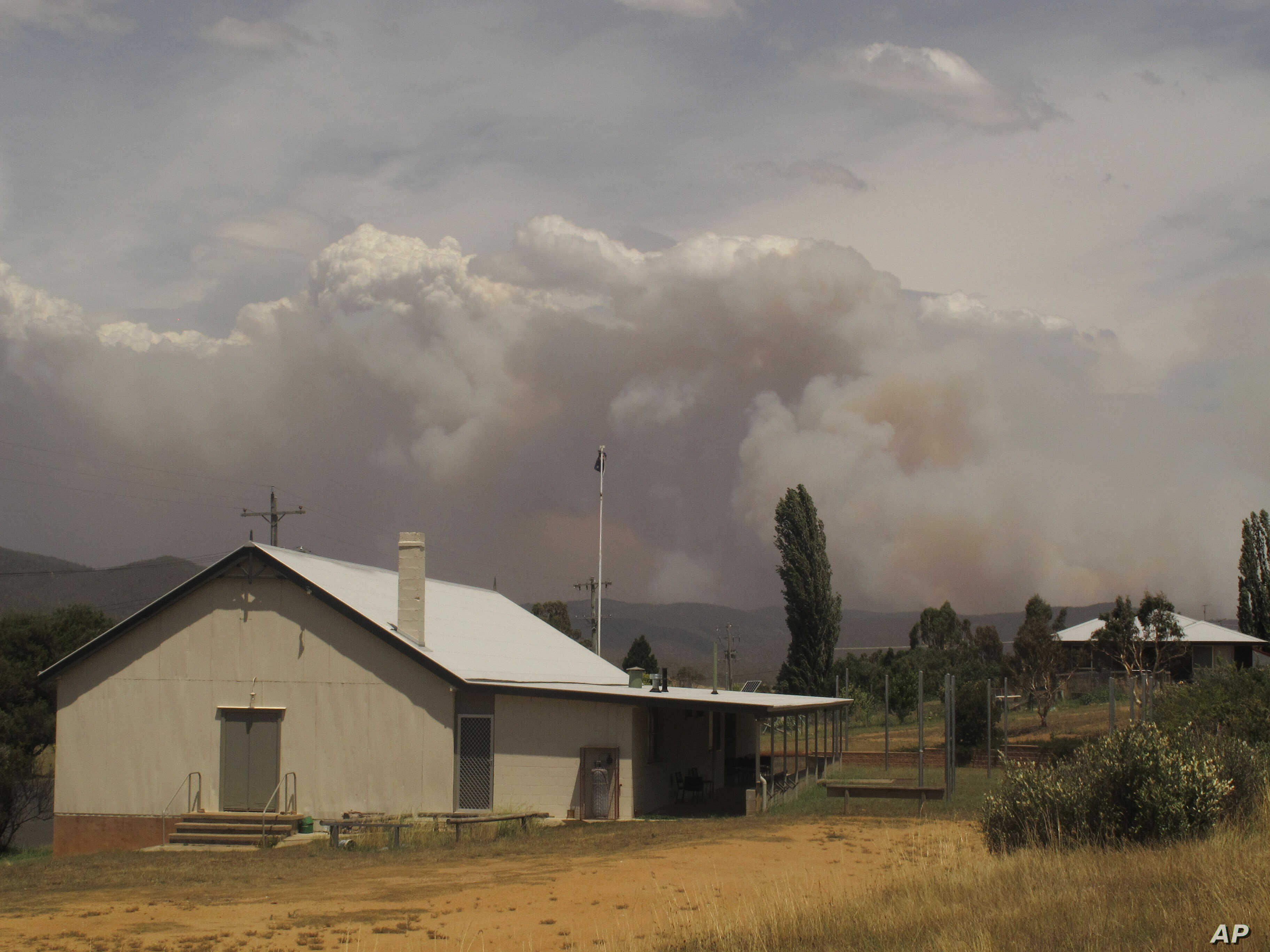 Wildfire smoke rises from hills behind the village of Numeralla in New South Wales state, Australia, January 8, 2013.