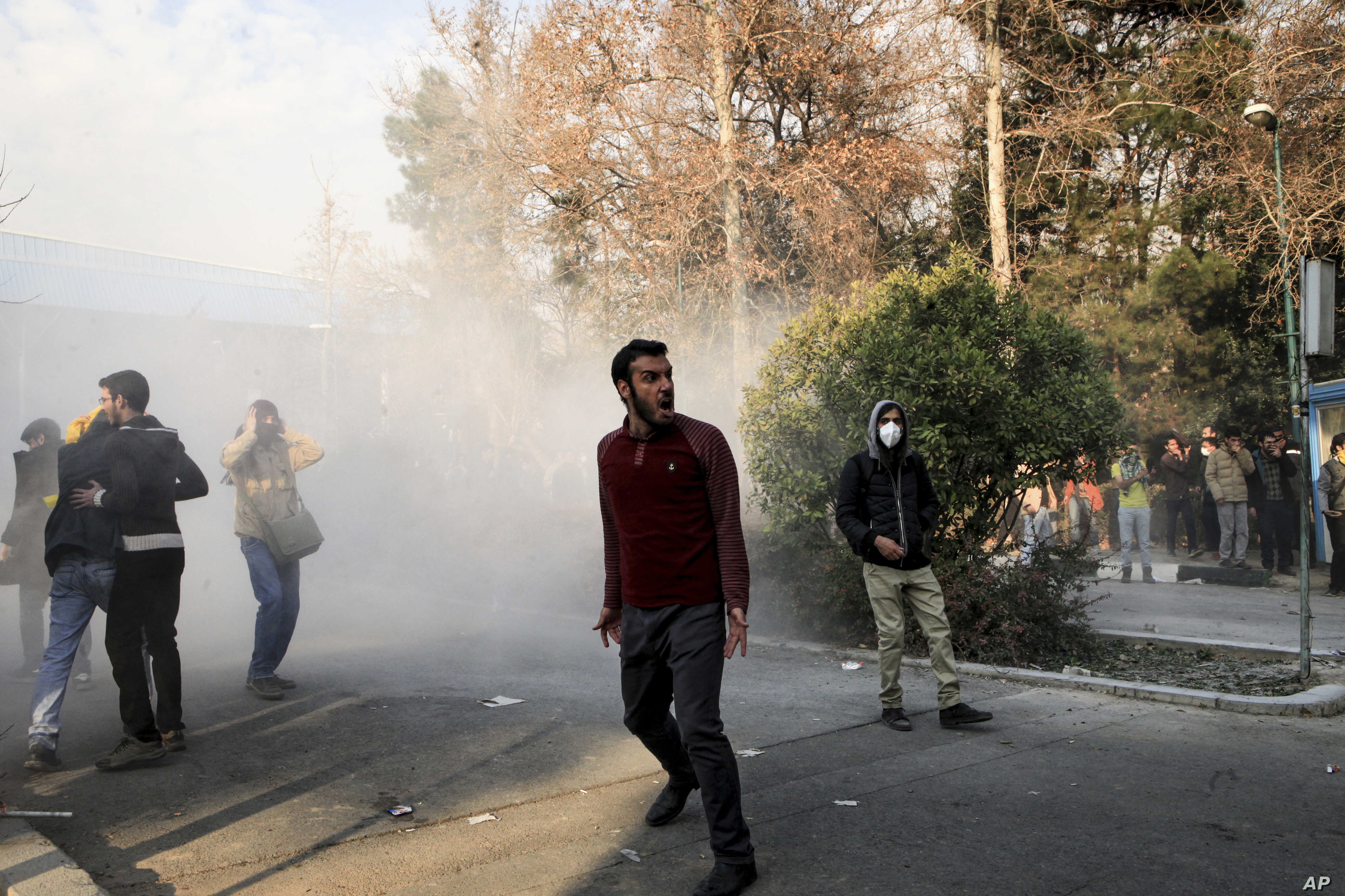 In this photo taken by an individual not employed by the Associated Press and obtained by the AP outside Iran, university students attend a protest inside Tehran University while a smoke grenade is thrown by anti-riot Iranian police, in Tehran, Dec. ...