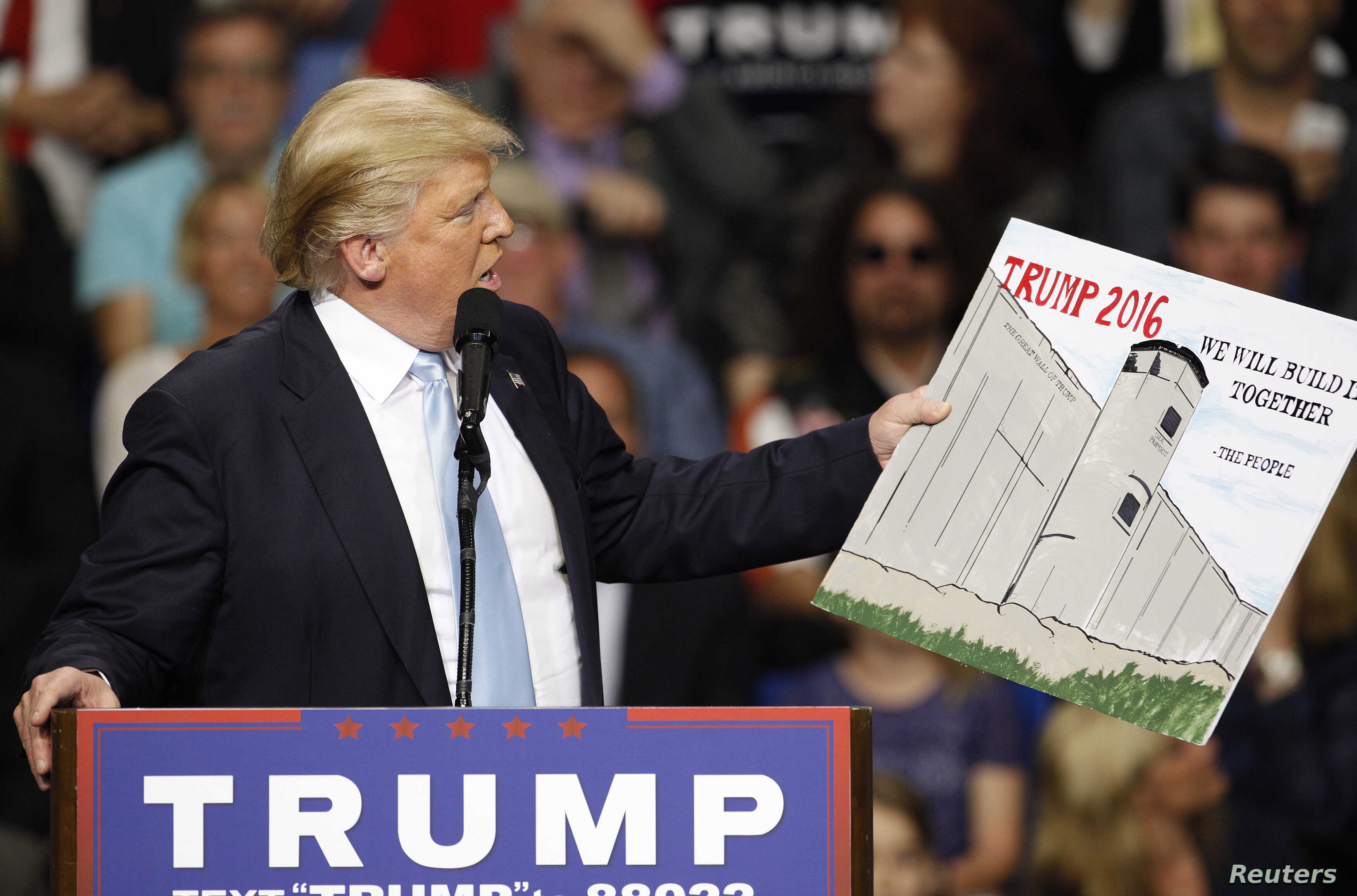 FILE - U.S. Republican presidential candidate Donald Trump holds a sign supporting his plan to build a wall between the United States and Mexico that he borrowed from a member of the audience at his campaign rally in Fayetteville, North Carolina,  Ma...
