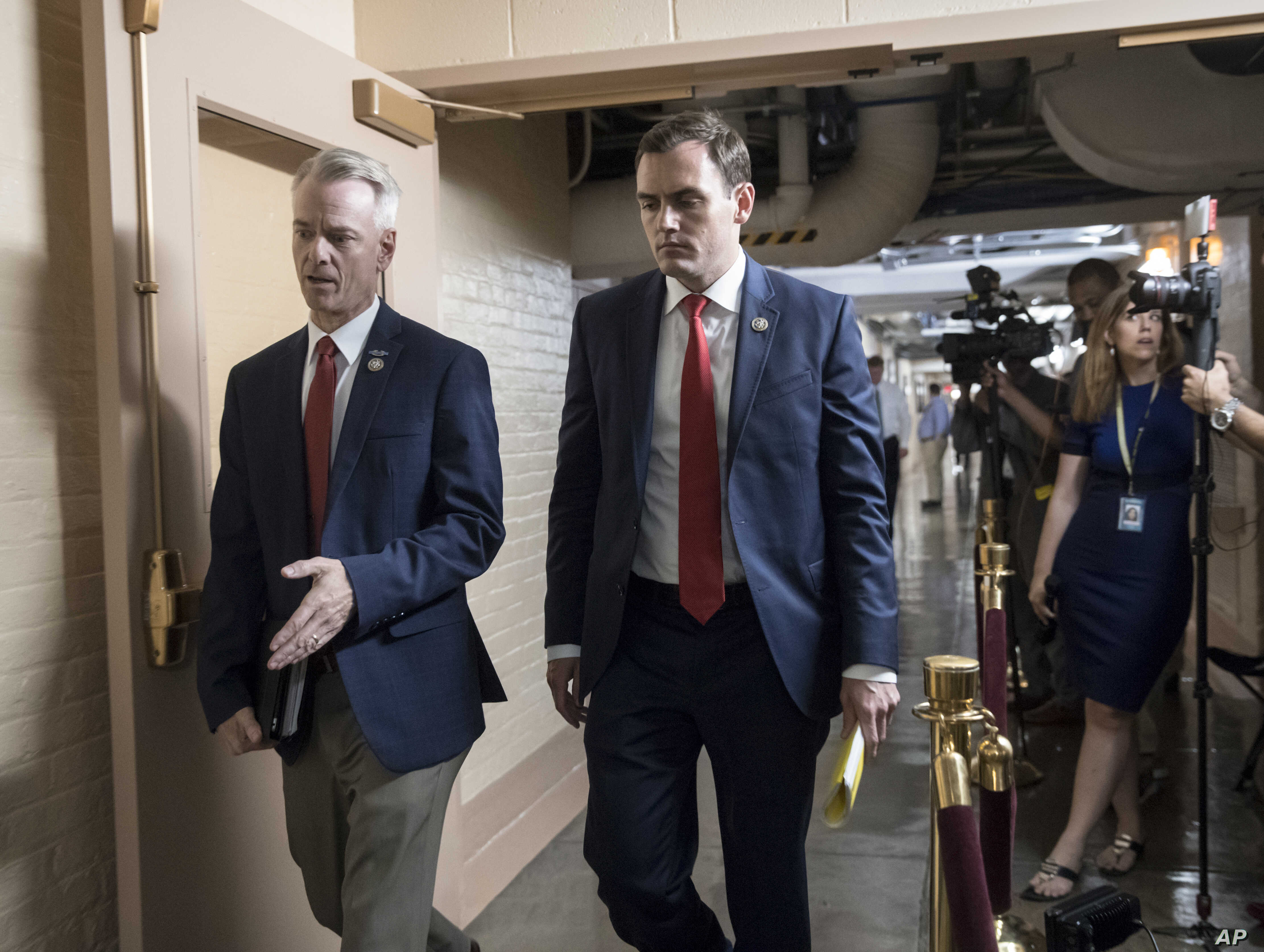 Rep. Steve Russell, R-Okla. (L), and Rep. Mike Gallagher, R-Wis., walk to a closed-door meeting with House Republicans seeking more information about compromise legislation on immigration, at the Capitol in Washington, June 21, 2018.