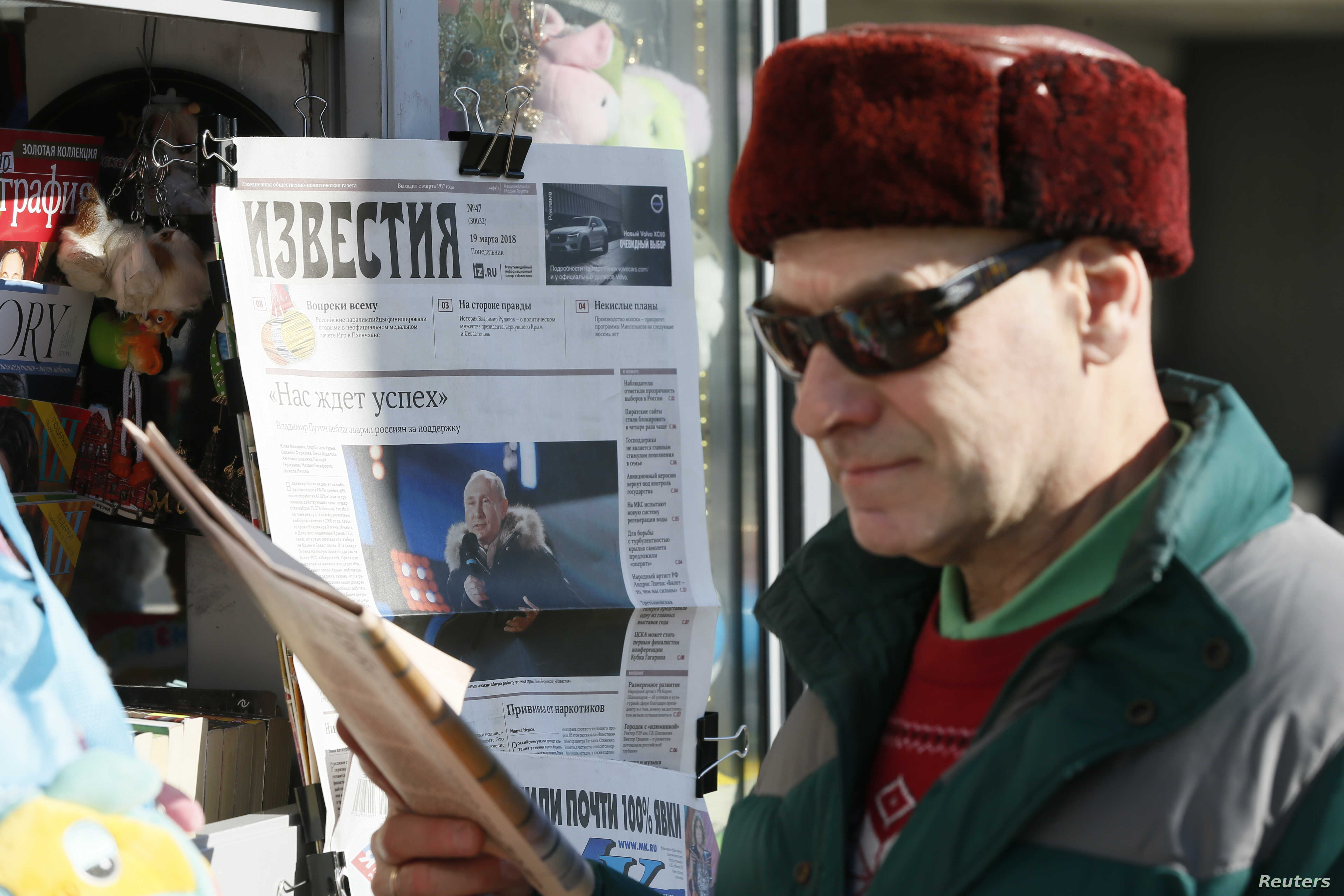 FILE - A man walks past a rack which displays a daily newspaper with a front page about Russian President Vladimir Putin's re-election victory on March 18, on a street in Moscow, Russia, March 19, 2018.