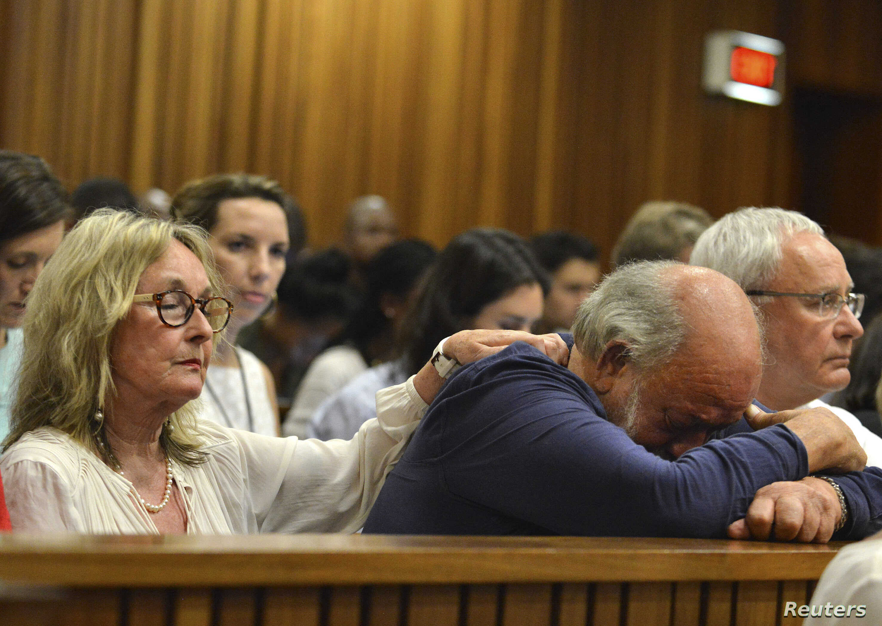 Barry Steenkamp, father of Reeva Steenkamp, is consoled by his wife June Steenkamp during the sentencing hearing of Olympic and Paralympic track star Oscar Pistorius at the North Gauteng High Court in Pretoria, Oct. 15, 2014.