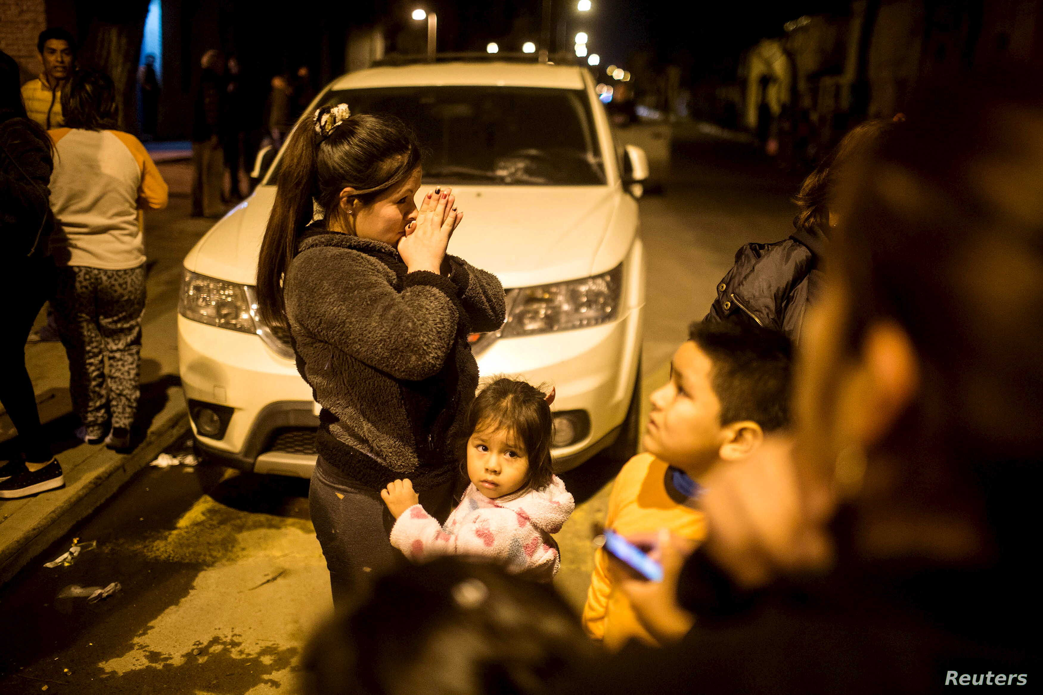 Residents stand on a street outside their houses after an earthquake hit Chile's central zone, Santiago, Sept. 16, 2015.