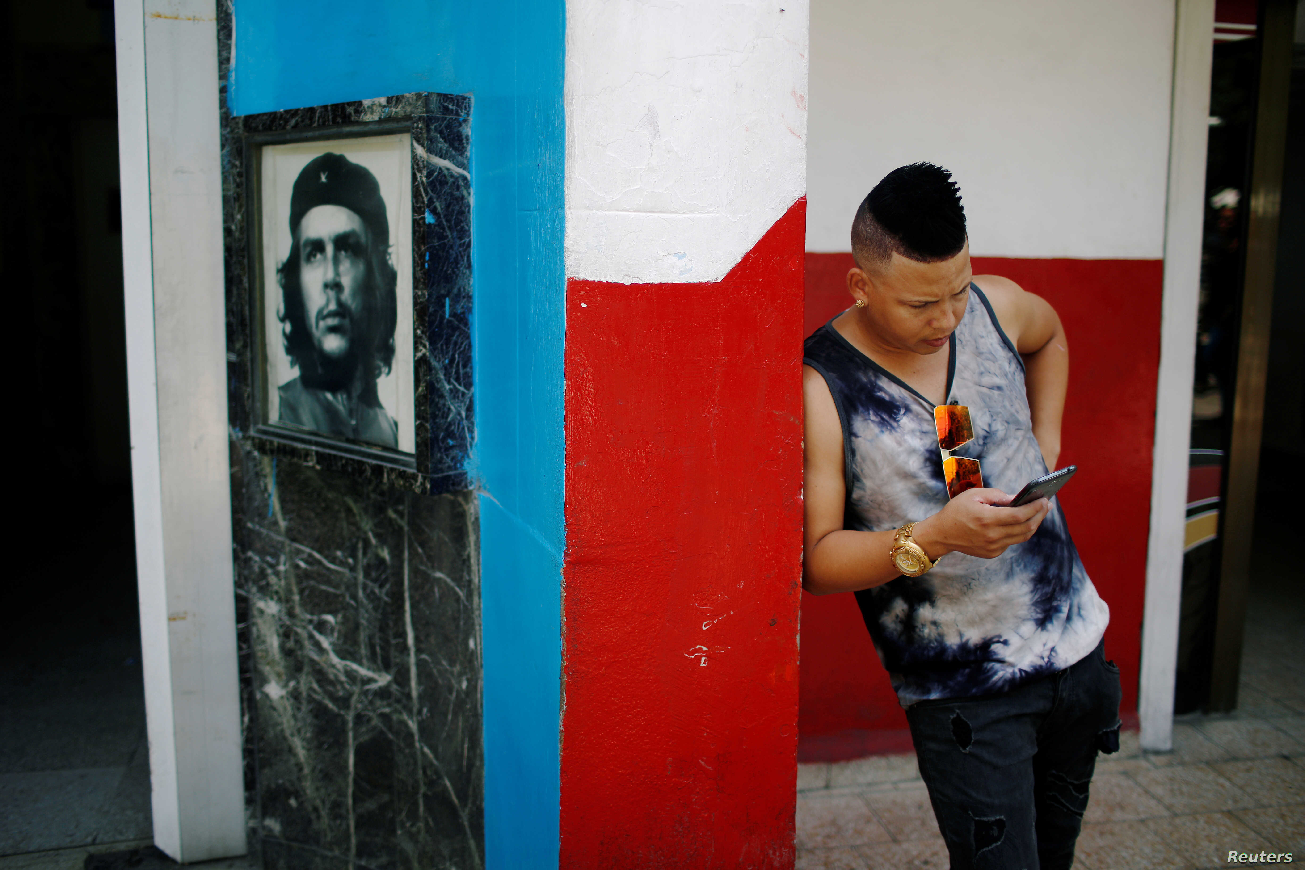 """A young Cuban checks his phone at an internet hotspot next to a picture of late revolutionary hero Ernesto """"Che"""" Guevara in Havana,  Aug. 10, 2018."""