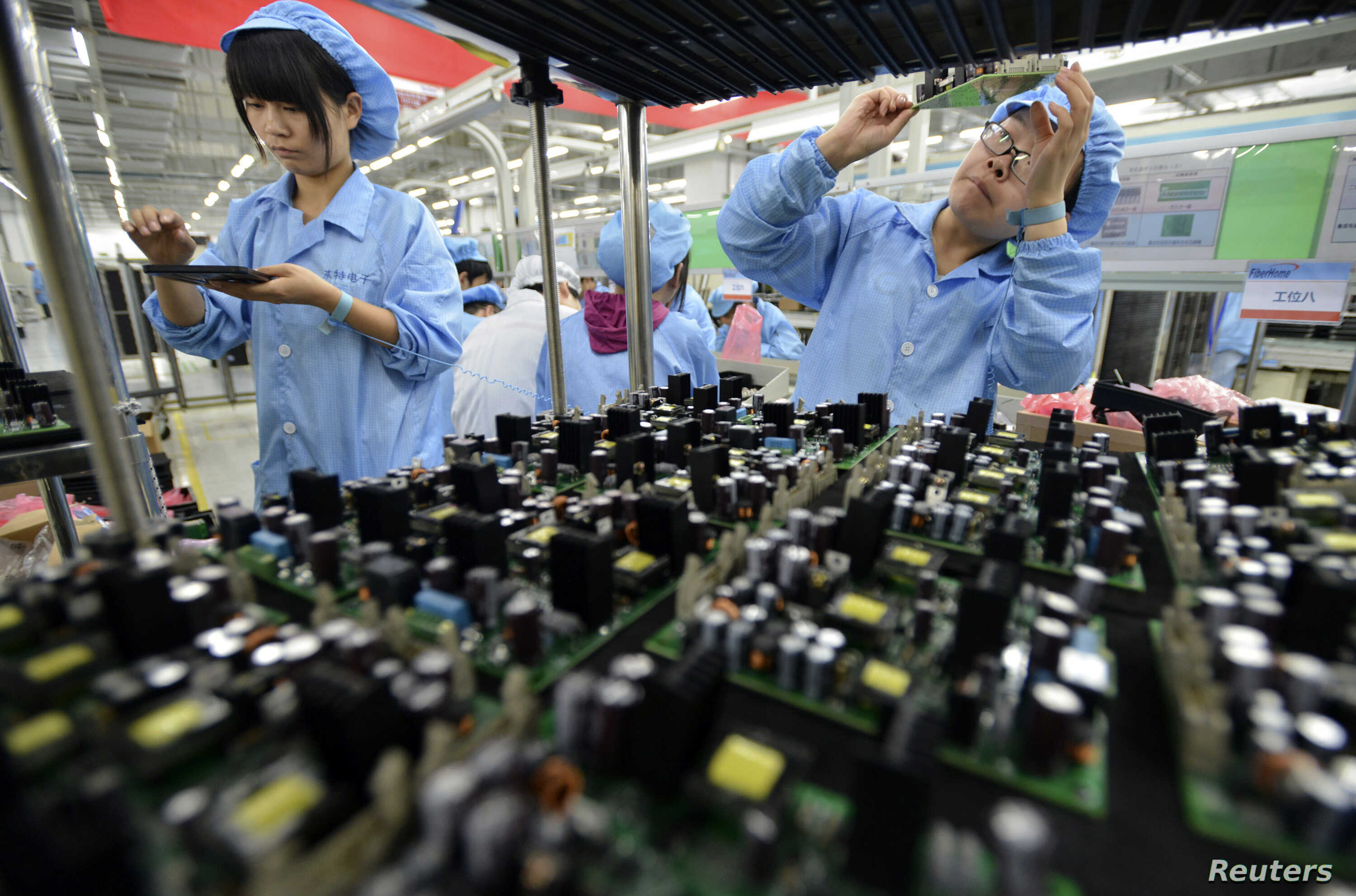 FILE - Employees work on a FiberHome Technologies Group factory production line in Wuhan, Hubei province, China, July 27, 2015. China relaxed its one-child policy Oct. 29, in part, to try to offset the country's shrinking workforce.