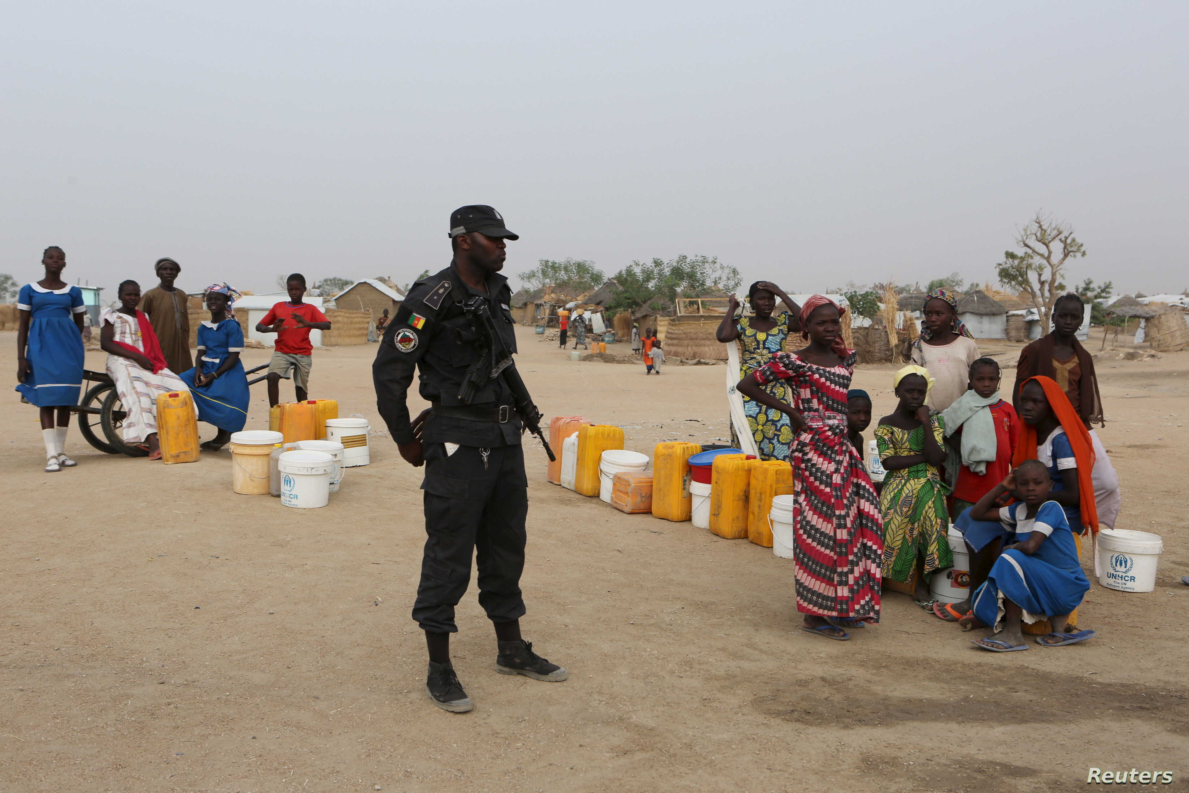 A Cameroonian police officer stands next to people waiting for water at the Minawao refugee camp for Nigerians who fled Boko Haram attacks in Minawao, Cameroon, March 15, 2016.