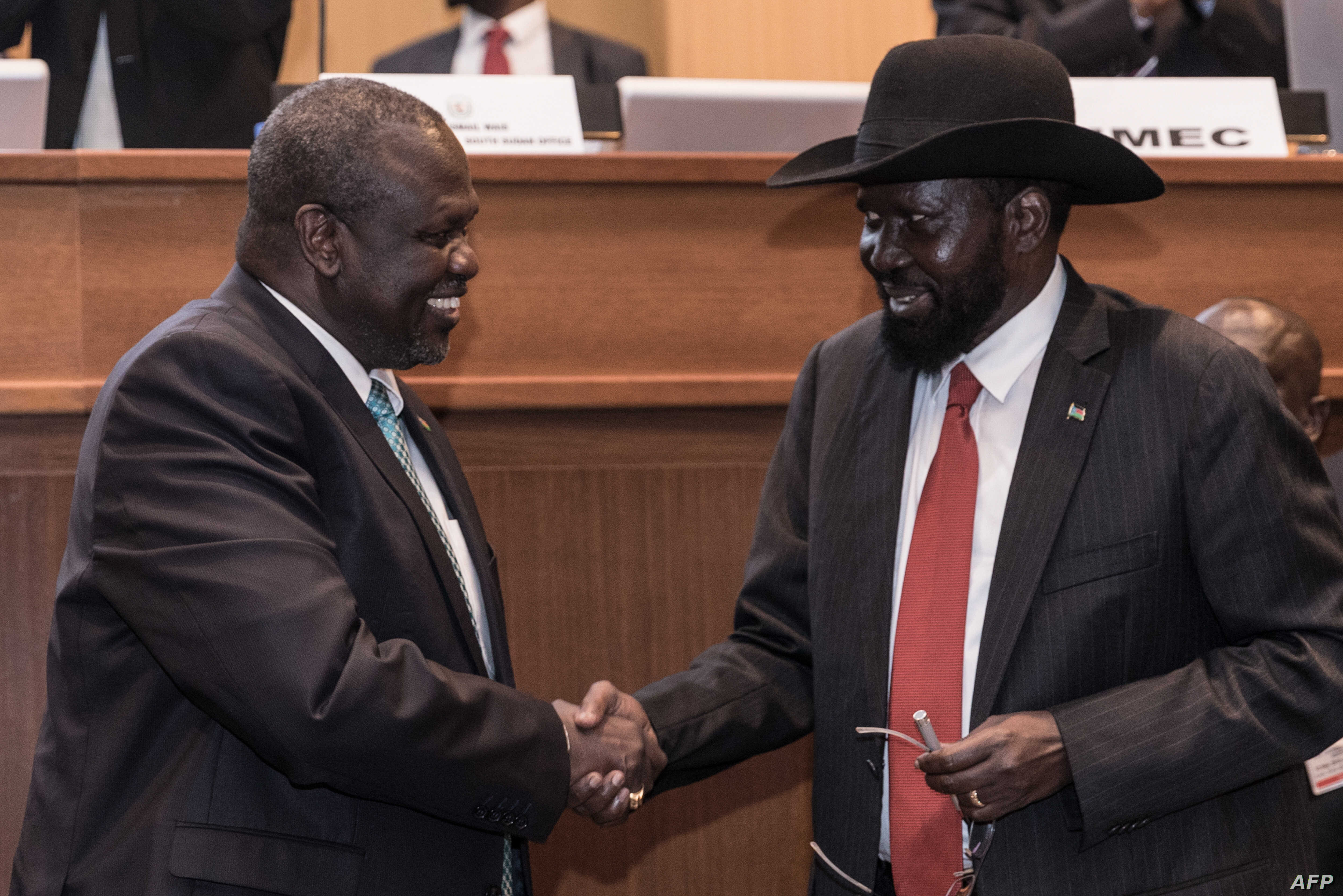 South Sudan's President Salva Kiir, right, and his former deputy turned rebel leader Riek Machar shake hands as they make a last peace deal at the 33rd Extraordinary Summit of Intergovernmental Authority on Development (IGAD) in Addis Ababa on Sept.1...