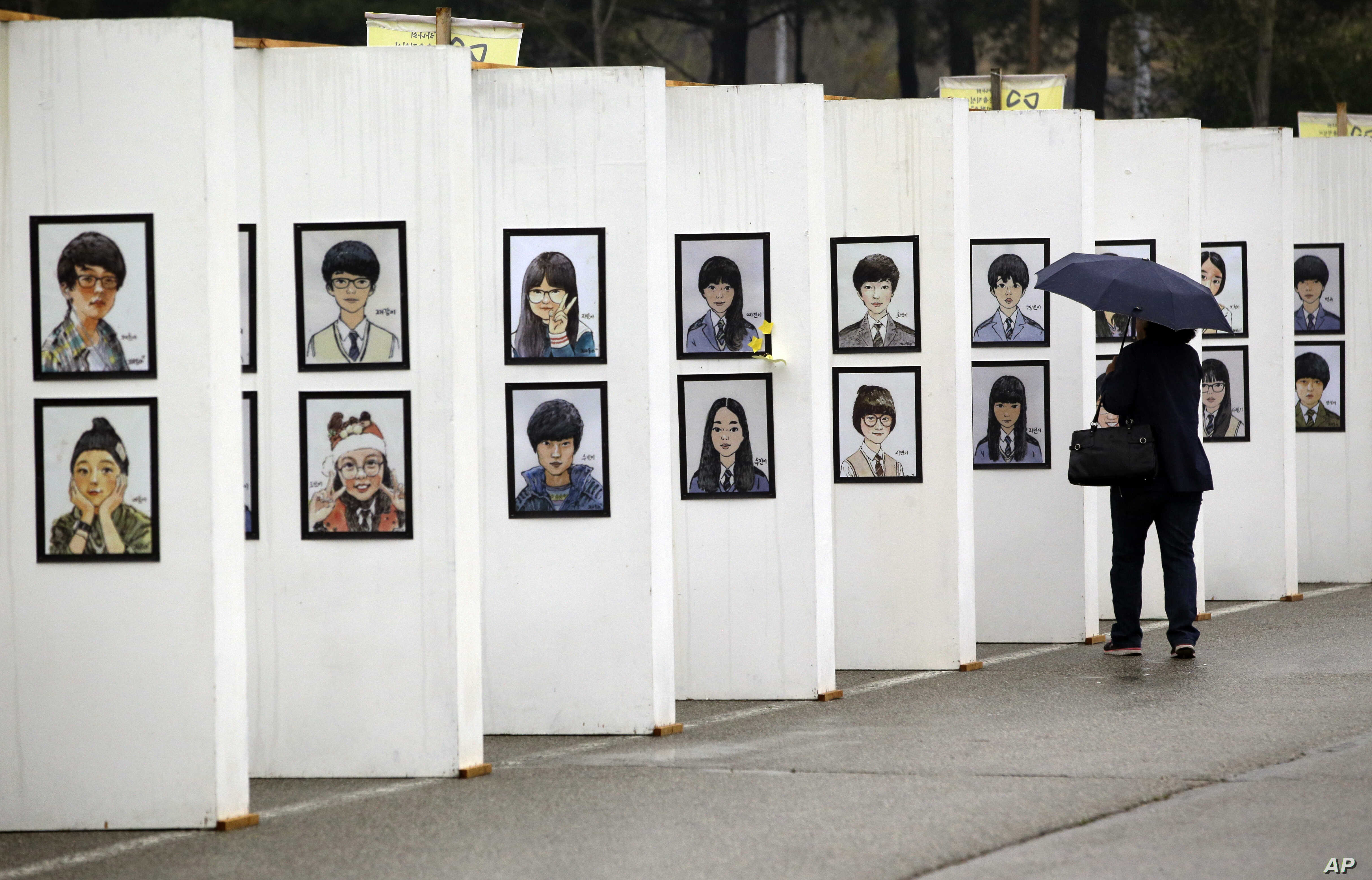 A woman looks at caricatures of the victims of the sunken ferry Sewol outside a group memorial altar in Ansan, South Korea, Thursday, April 16, 2015. Tears and grief mixed with raw anger Thursday as black-clad relatives mourned the 300 people, mostly...