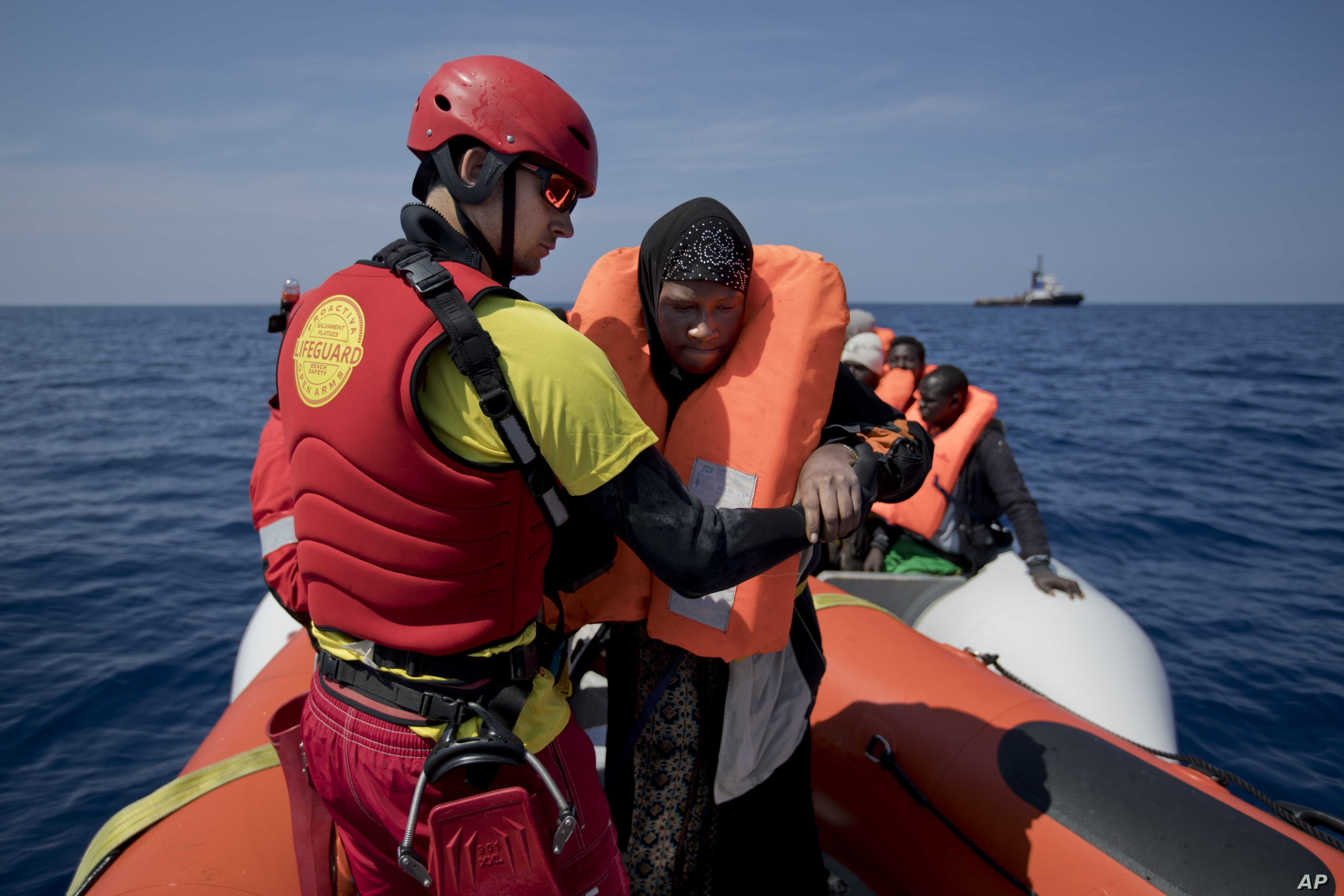 FILE - Proactiva Open Arms lifeguard Ivan Martinez, from Spain, rescues migrants from a rubber boat sailing out of control, in the Mediterranean Sea, about 56 miles north of Sabratha, Libya, April 6, 2017. Spain's maritime rescue service says it resc...