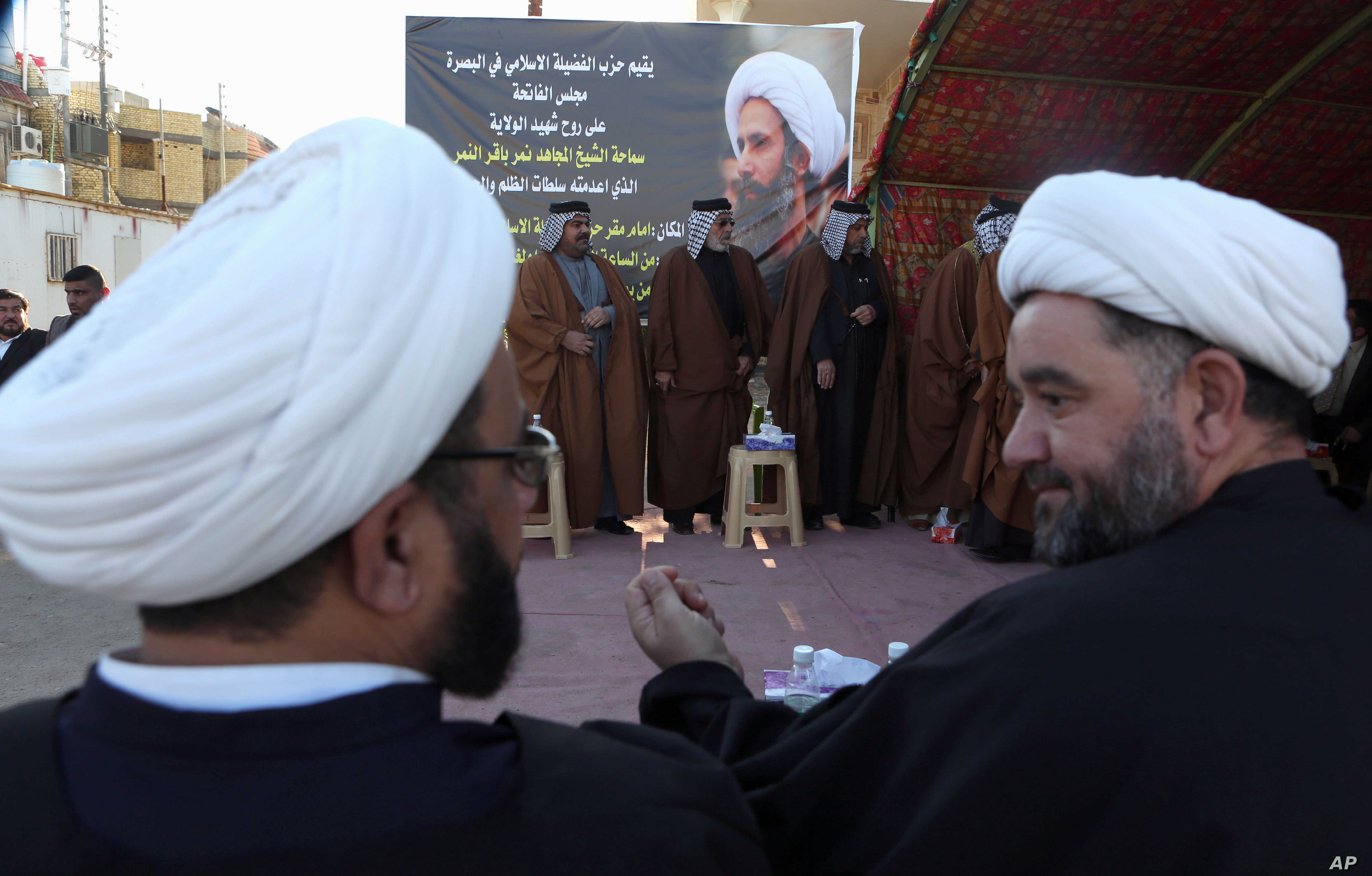 Iraqi Shiite clerics,foreground, attend a symbolic funeral for Sheik Nimr al-Nimr, seen in background photo, a prominent opposition Shiite cleric convicted of terrorism charges and executed by Saudi Arabia, in Basra, Iraq, Jan. 3, 2016.