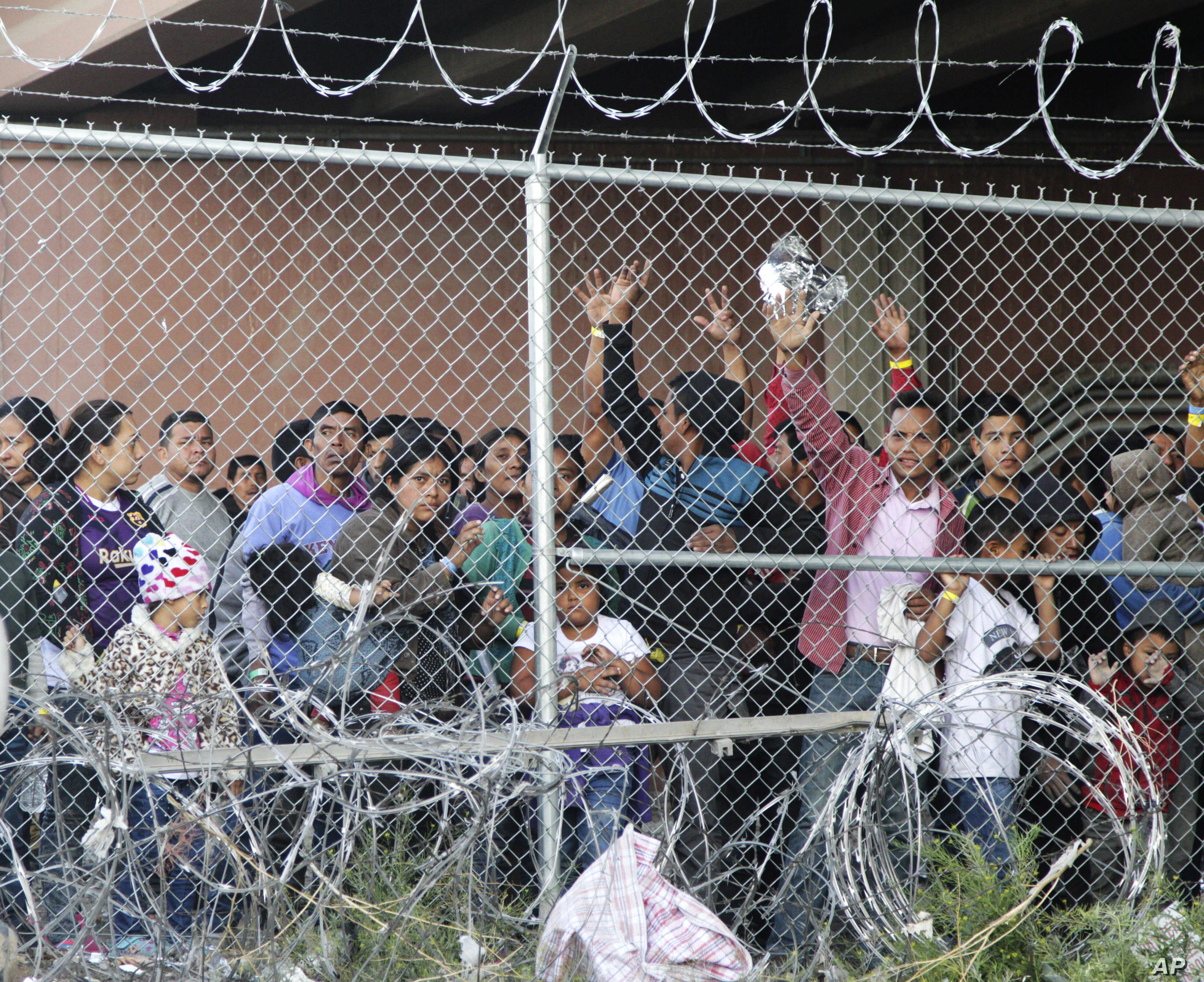 Central American migrants wait for food in El Paso, Texas, March 27, 2019, in a pen erected by U.S. Customs and Border Protection to process a surge of migrant families and unaccompanied minors.