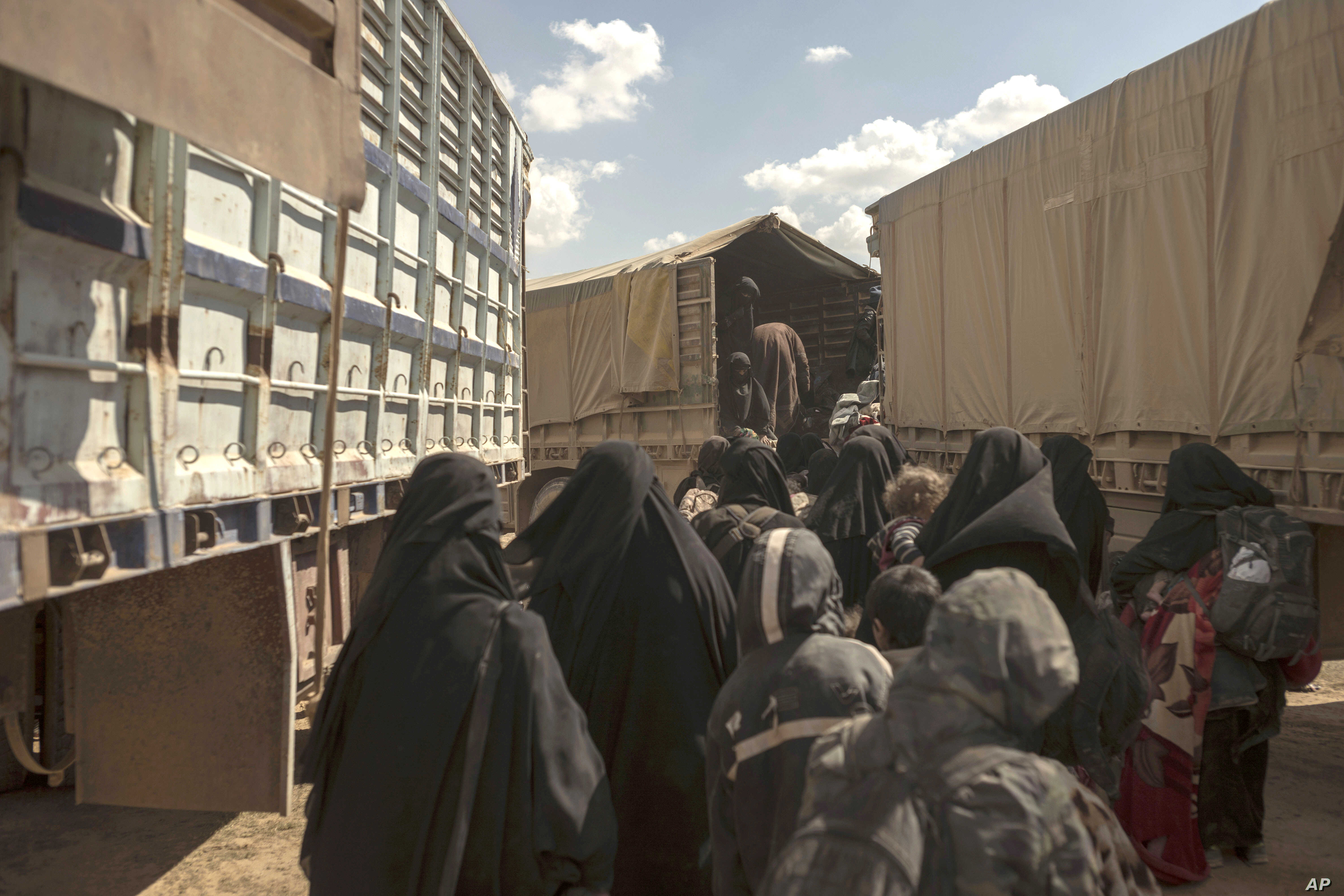 Women and children board a truck at a reception area for people evacuated from the last shred of territory held by Islamic State militants, outside Baghuz, Syria, March 6, 2019.