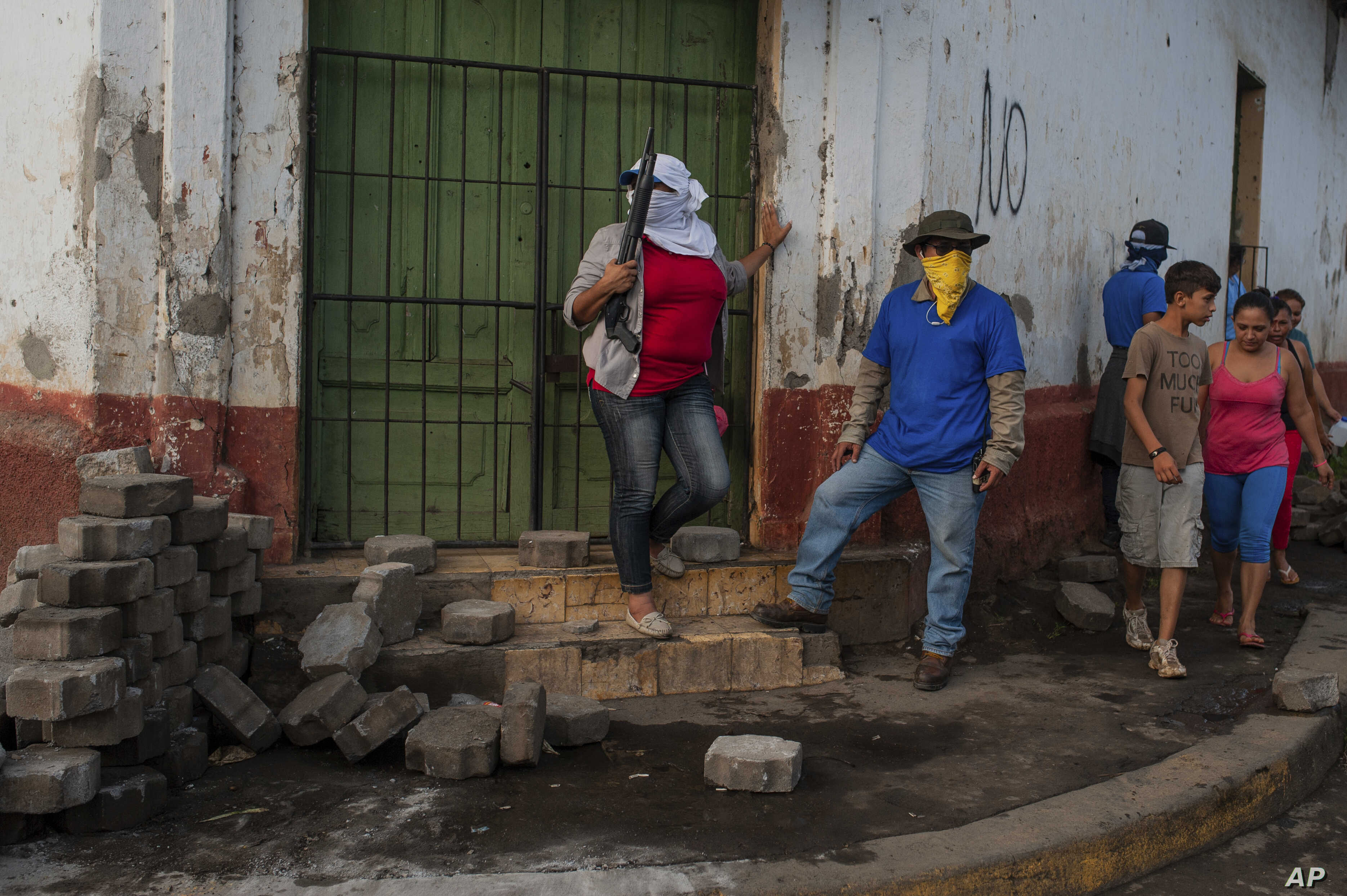 Sandinista militias stand guard at a torn down barricade after police and pro-government militias stormed the Monimbo neighborhood of Masaya, Nicaragua, Tuesday, July 17, 2018.