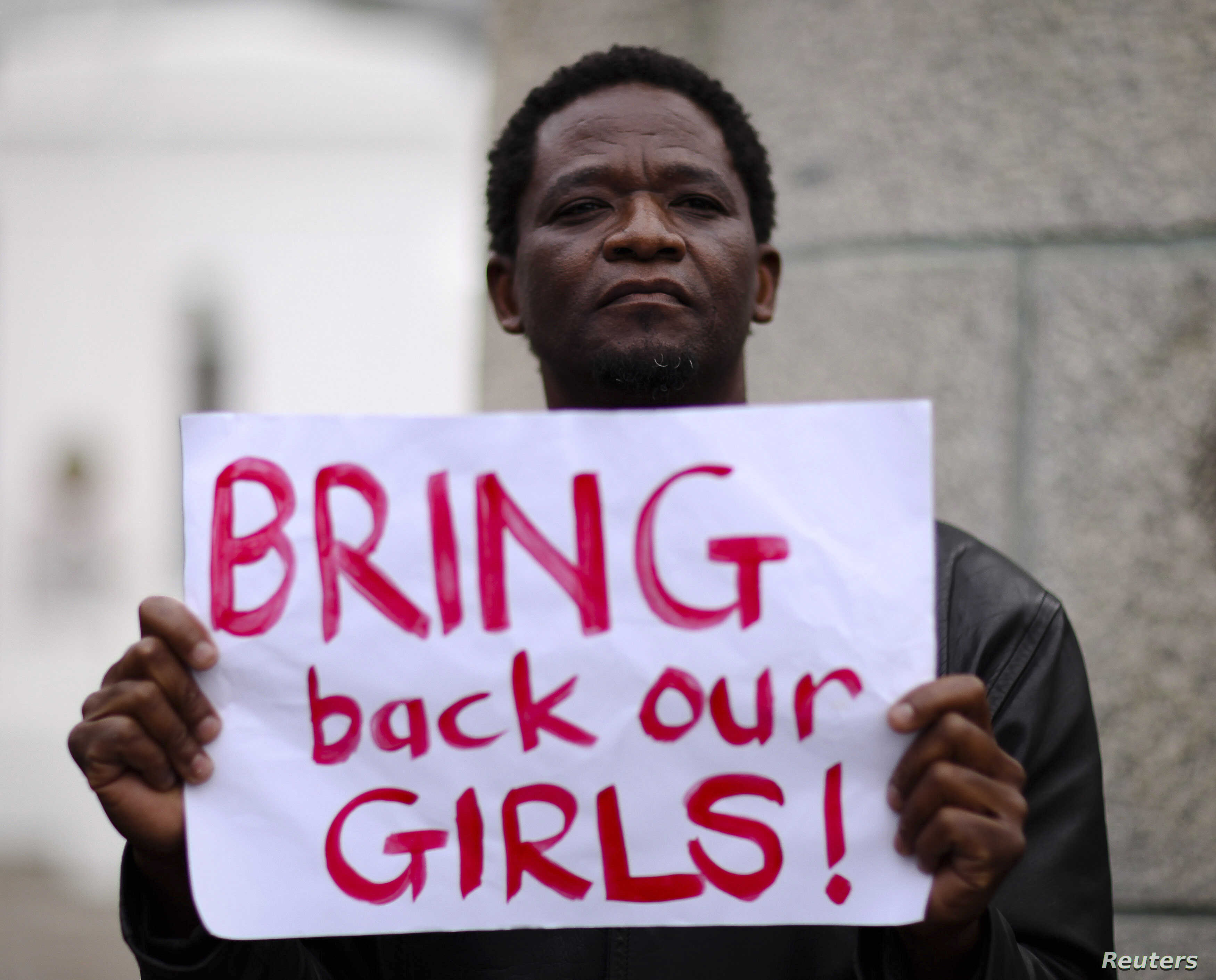 A protester holds a sign during a march in support of the girls kidnapped in Nigeria by members of Boko Haram, in Cape Town, May 8, 2014.