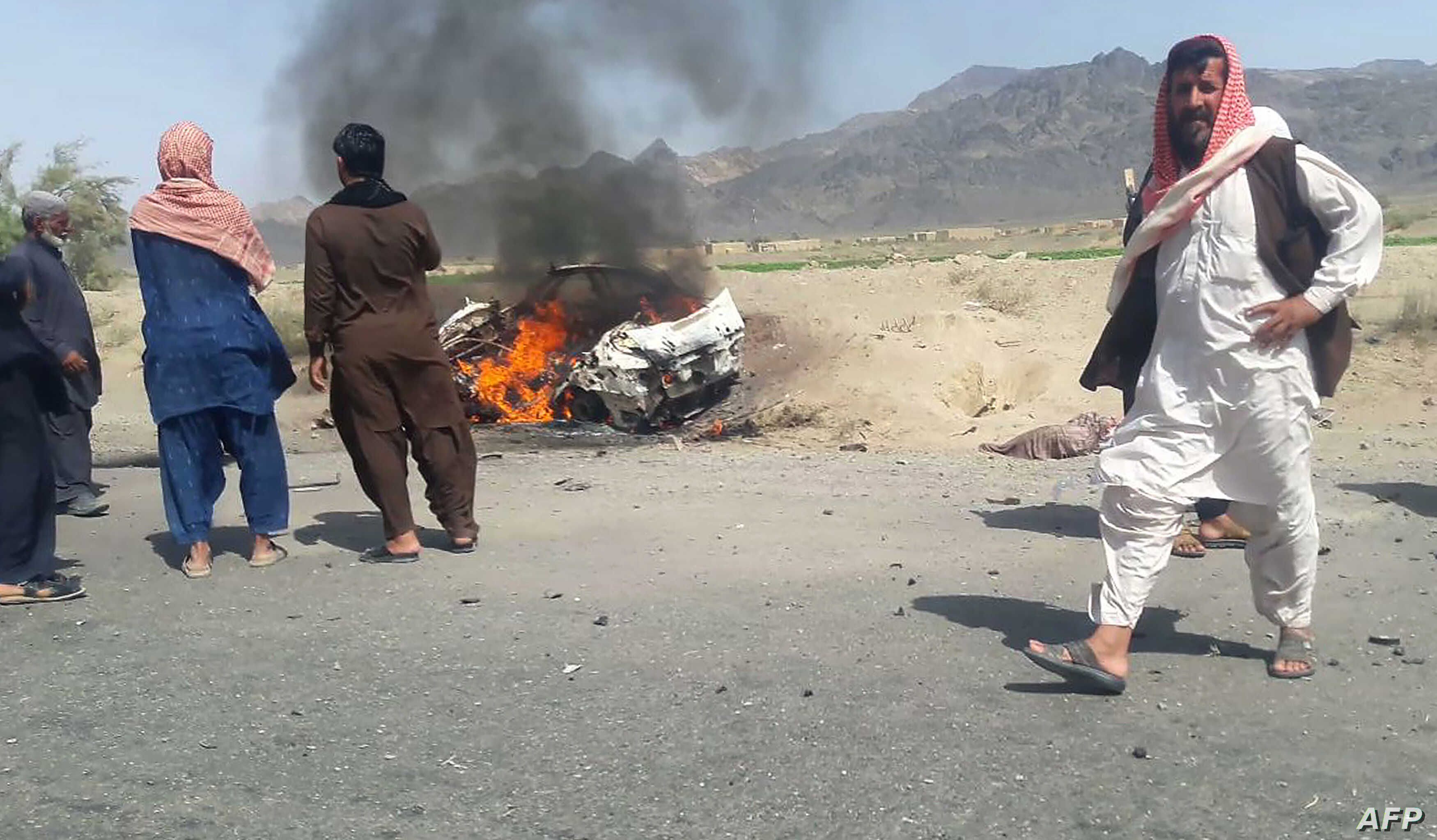 Pakistani local residents gather around a burning vehicle hit by a U.S. drone strike, May 21, 2016. Afghan Taliban Mullah Akhtar Mansoor was the target of the drone near Dalbandin, Baluchistan, Pakistan.