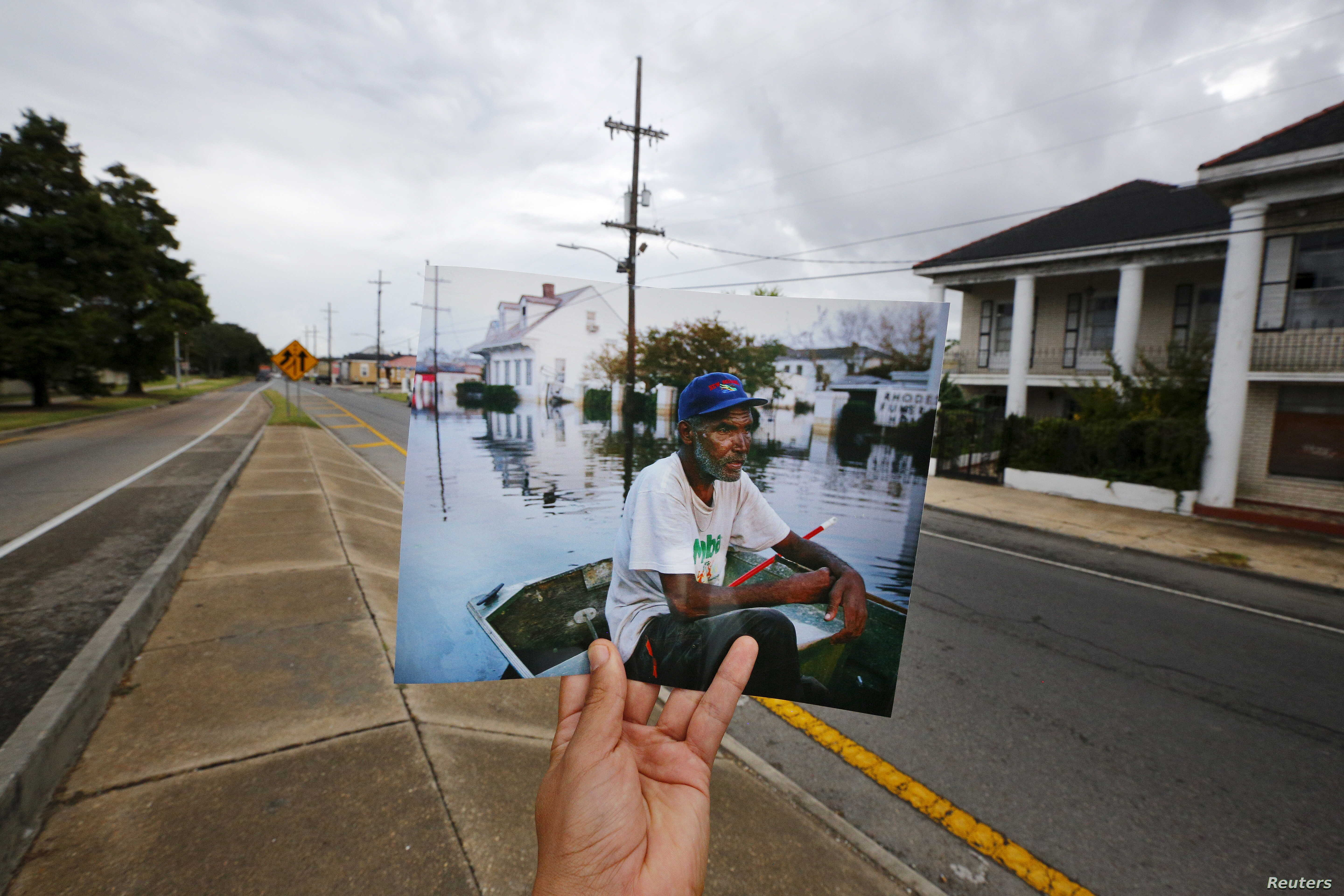 FILE - Photographer Carlos Barria holds a print of a photograph he took in 2005, as he matches it up at the same location 10 years on, in New Orleans, Aug. 16, 2015.