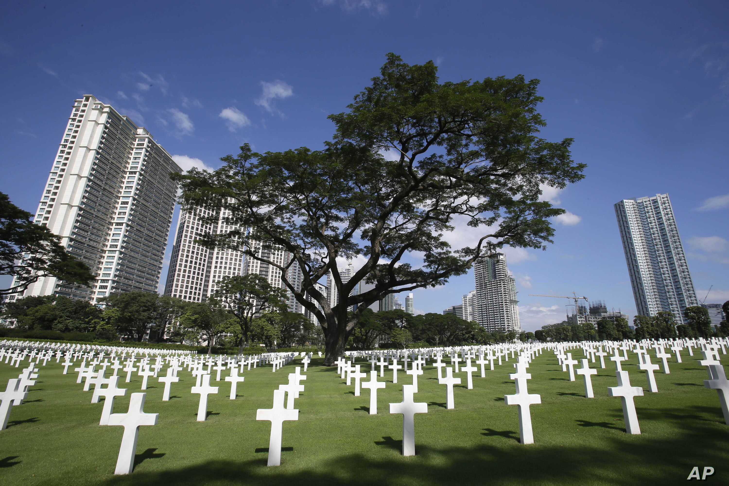 FILE - Rows of crosses totaling 16,933 Latin crosses, 164 Stars of David and 3,740 unknowns, dot the 152-acre American Cemetery as U.S. and Filipino WWII veterans and other officials (unseen) commemorate U.S. Veterans Day at the American Cemetery at ...