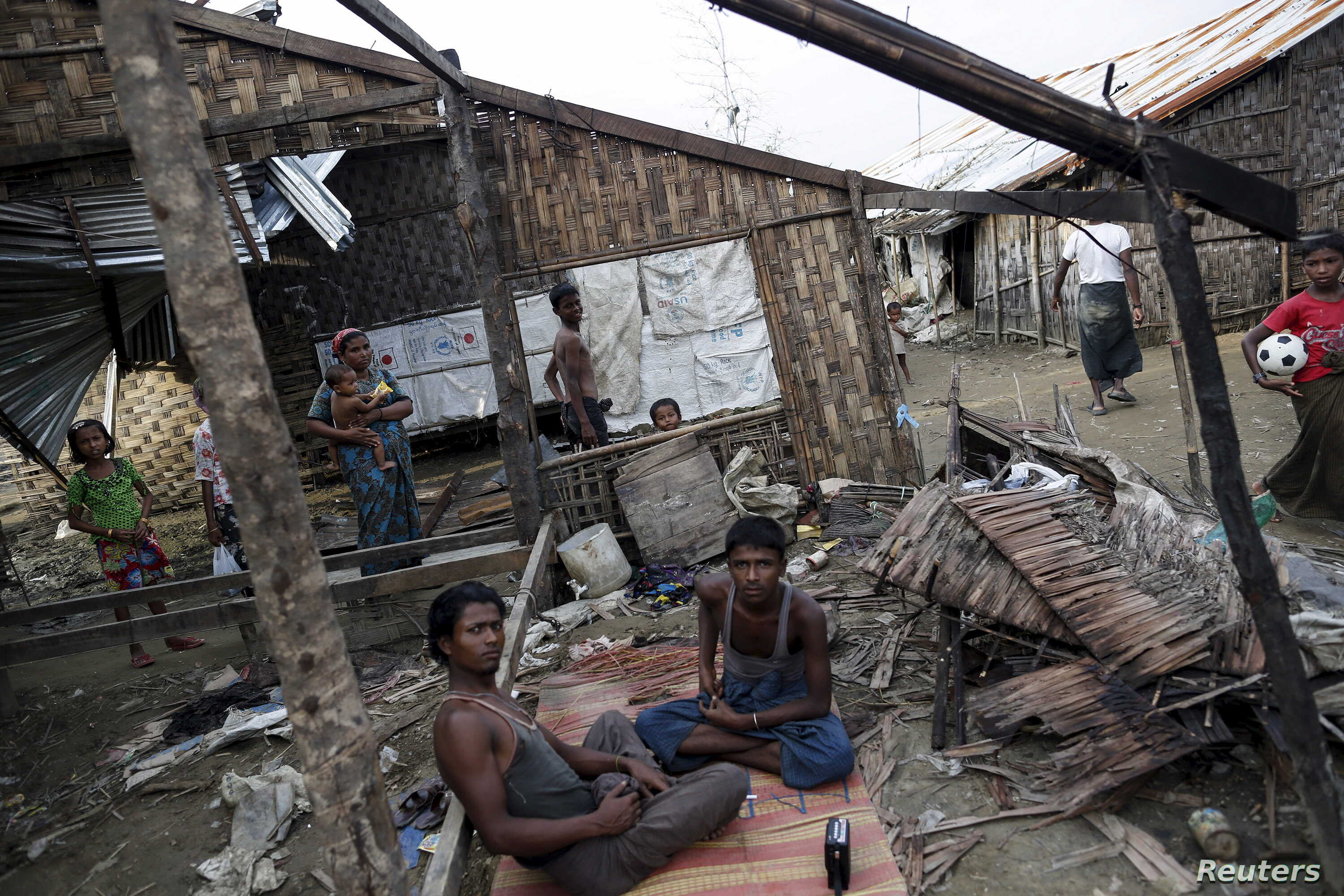 FILE - Rohingya people pass their time in a damaged shelter in Rohingya IDP camp outside Sittwe, Rakhine state, Aug. 4, 2015.