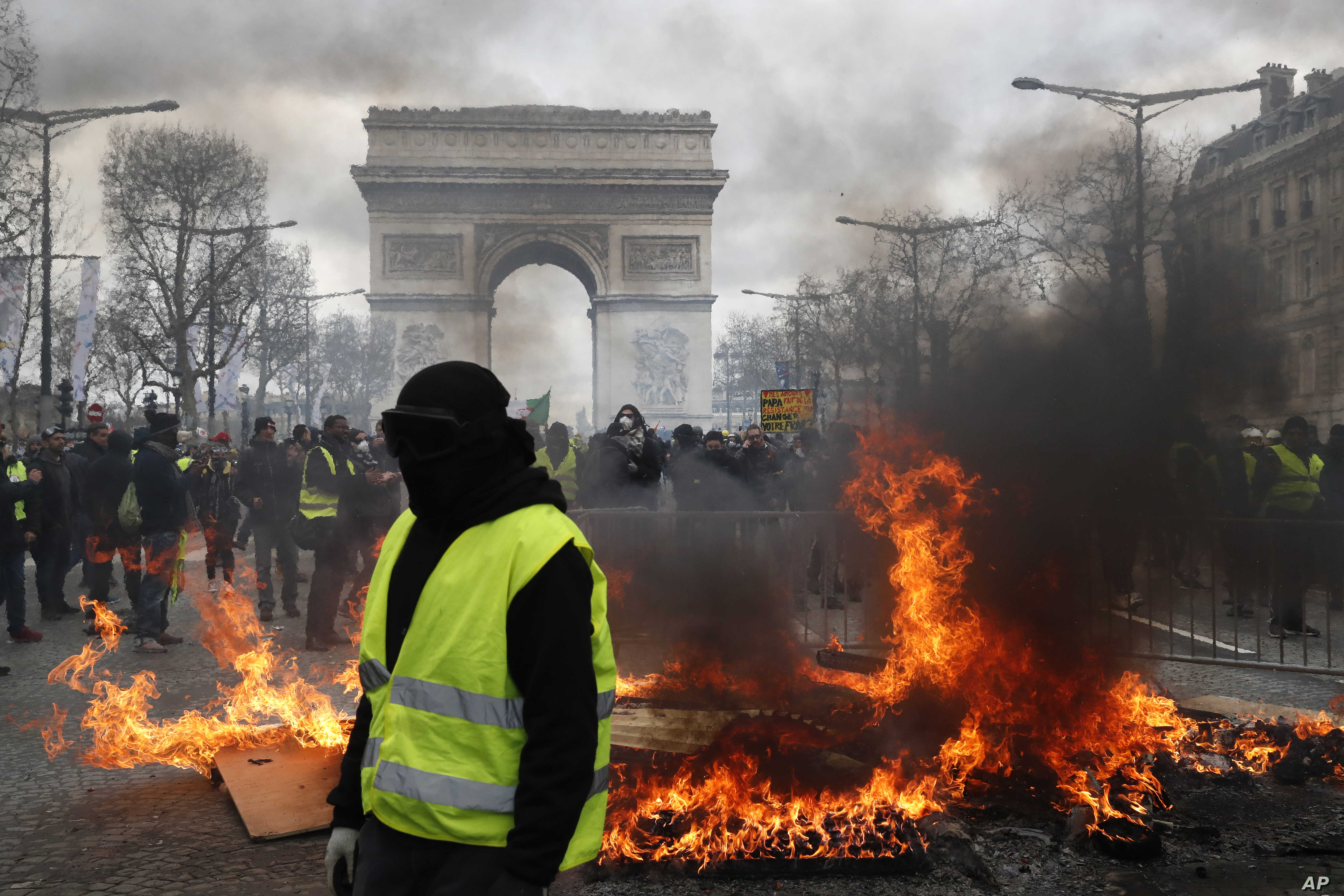 A yellow vest protester walks past a fire on Champs Elysees avenue in Paris, France, March 16, 2019.