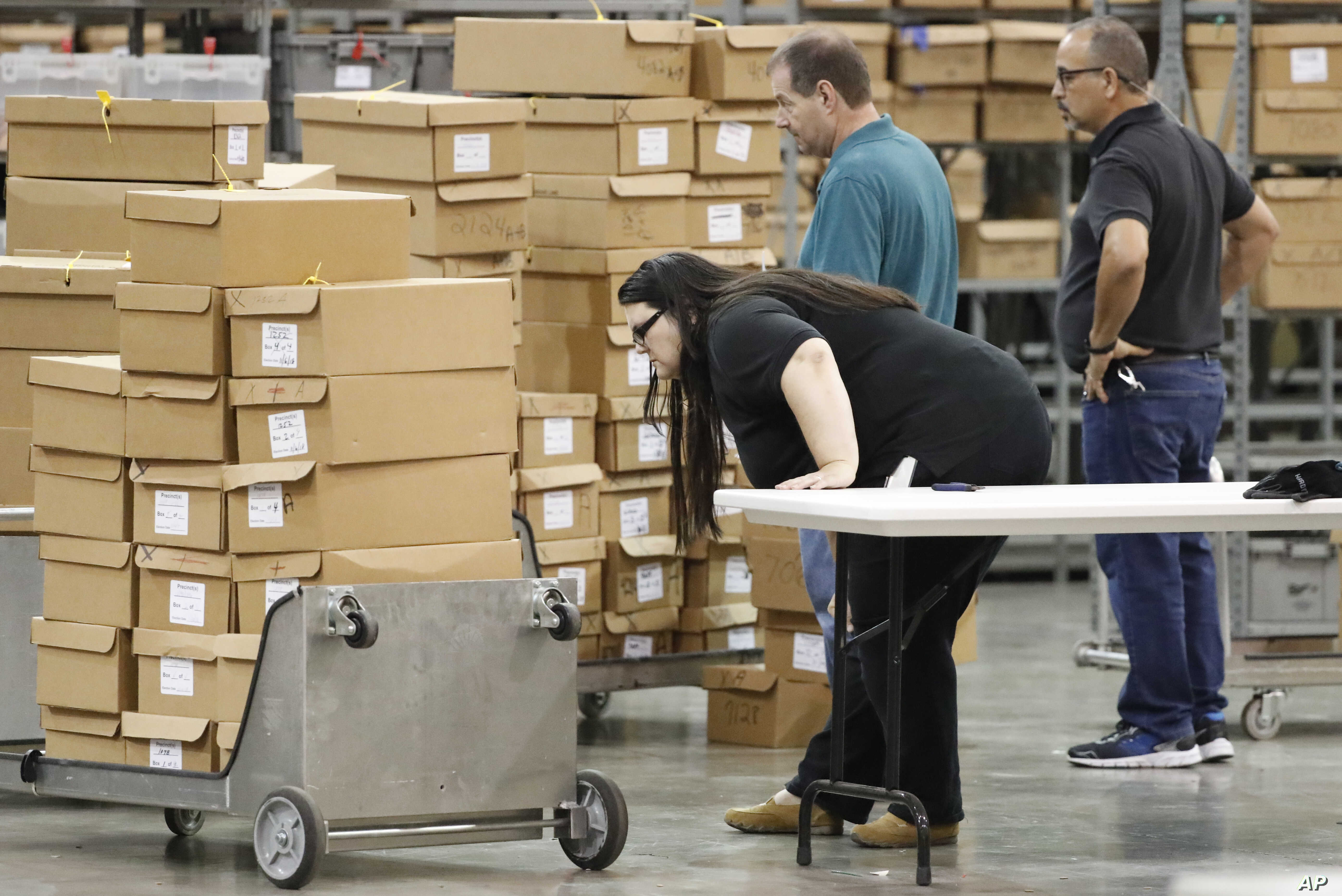 Employees prepare to unpack boxes of ballots before resuming a recount at the Palm Beach County Supervisor of Elections office, Nov. 15, 2018, in West Palm Beach, Florida.