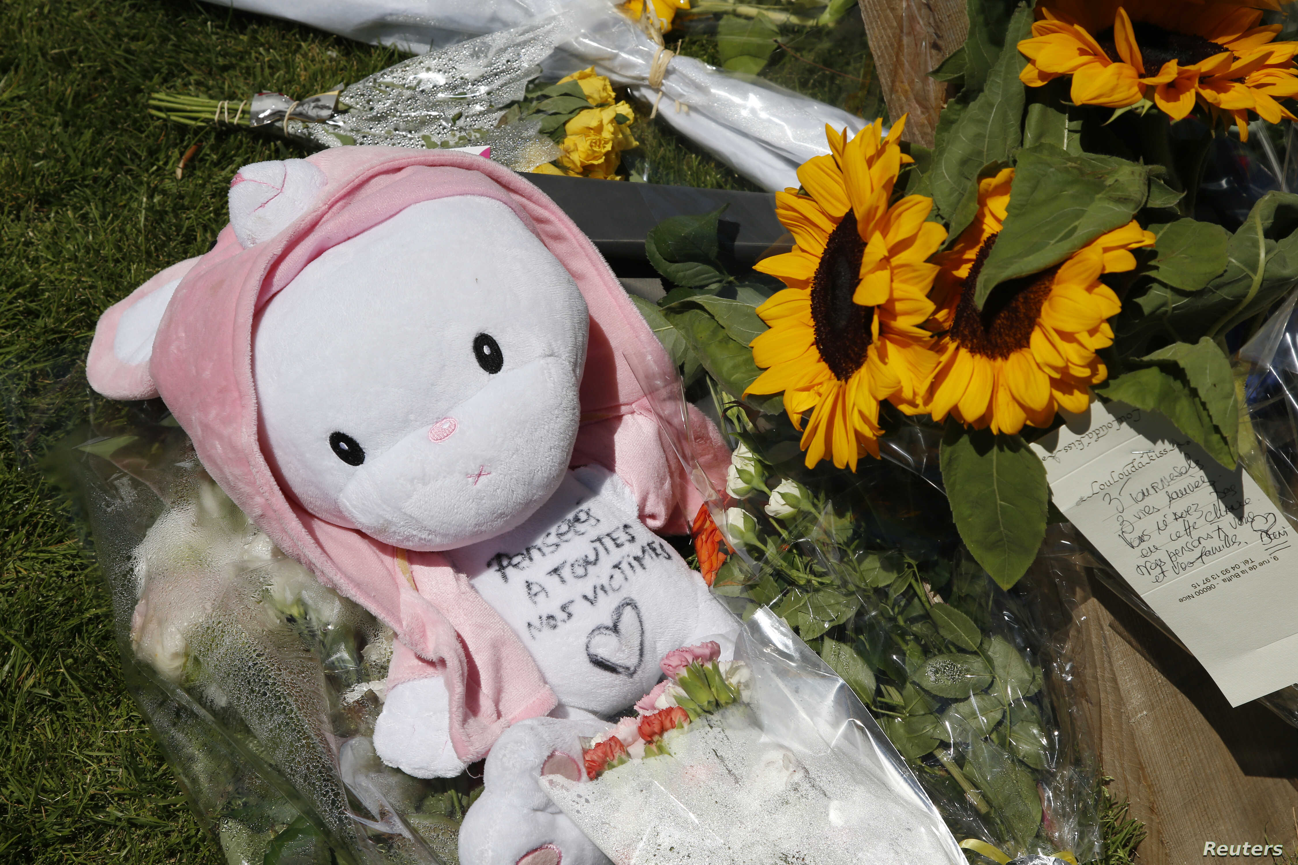 """A child's stuffed toy with the message, """"Thoughts to All the Victims"""" is seen as people pay tribute near the scene where a truck ran into a crowd at high speed killing scores and injuring more who were celebrating the Bastille Day national holiday, i..."""