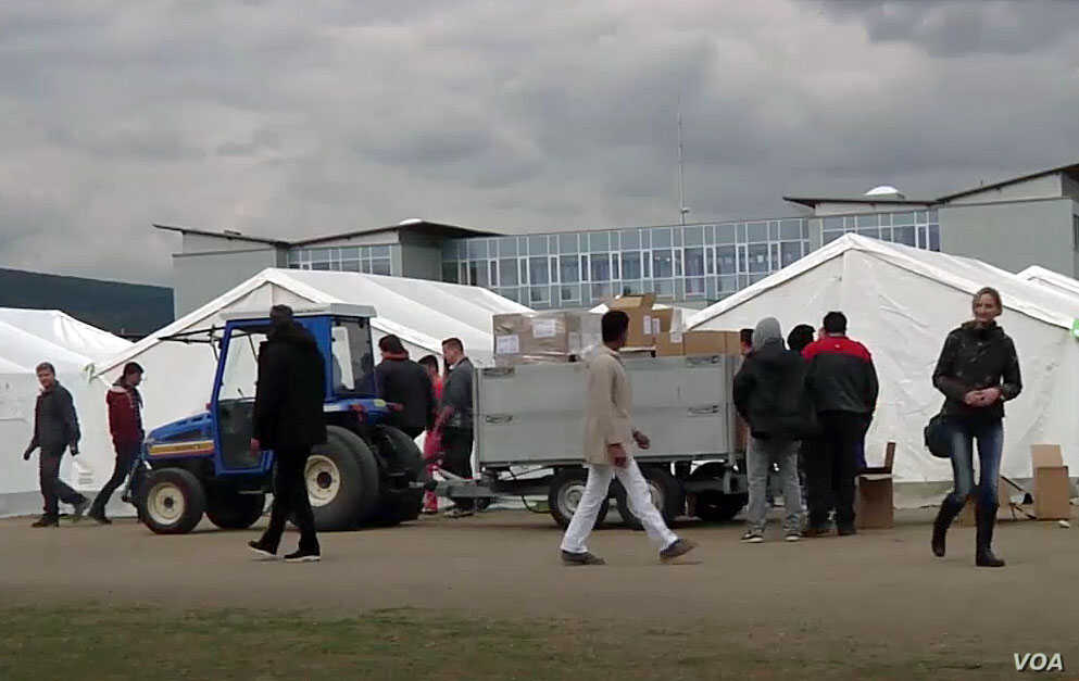 A tractor is seen transporting supplies through the make-shift reception center for migrants and asylum-seekers in Traiskirchen, Austria. (Photo - VOA video grab)