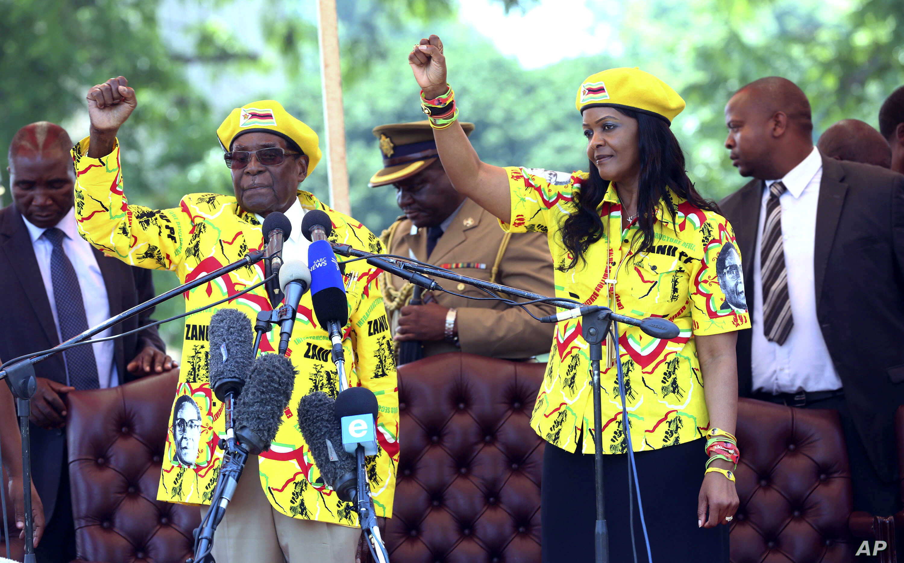 Zimbabwe's President Robert Mugabe, left, and his wife Grace chant the party's slogan during a solidarity rally in Harare, Wednesday, Nov. 8, 2017.