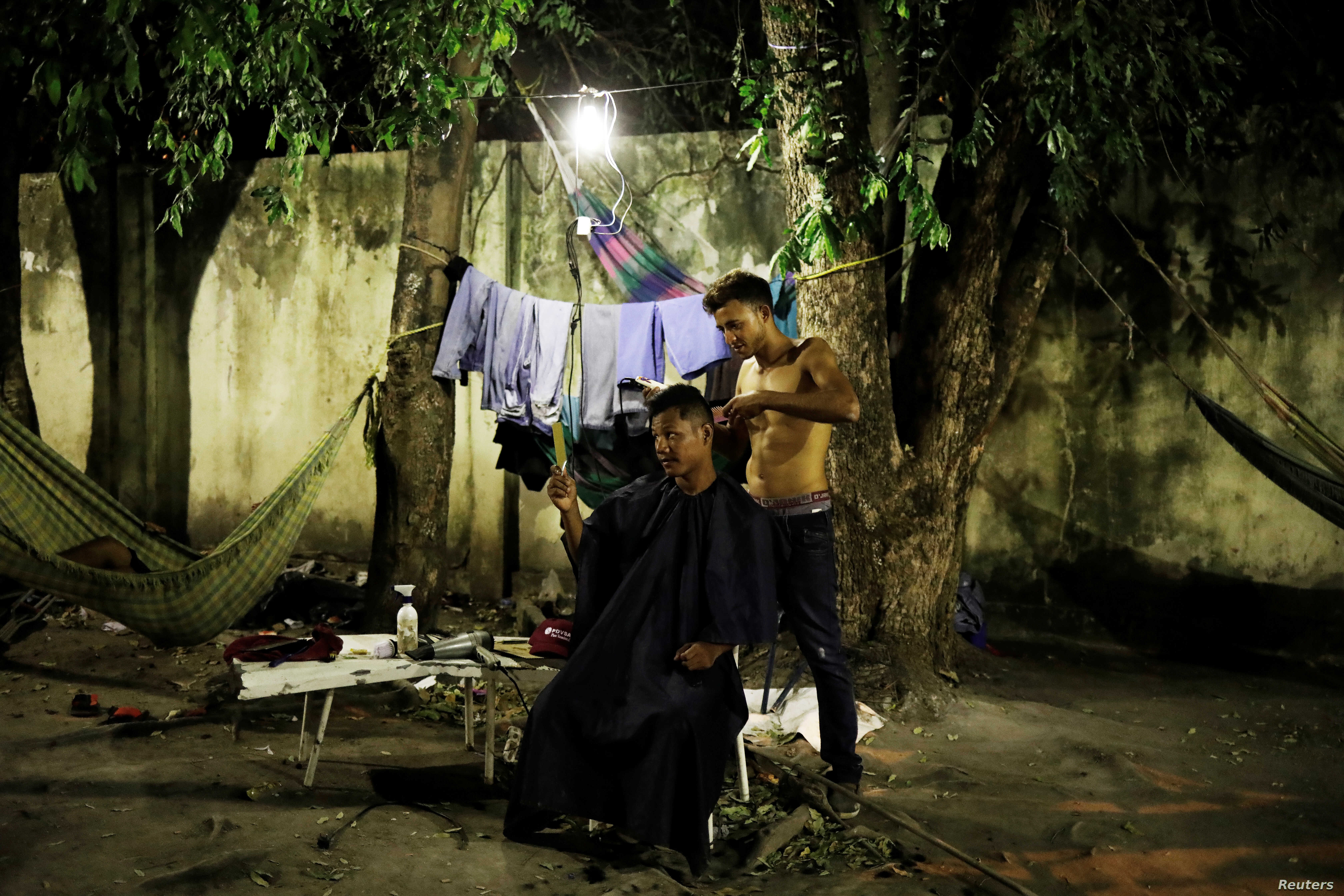 A Venezuelan man cuts the hair of his friend at a gym which has turned into a shelter for Venezuelans in Boa Vista, Brazil Nov. 17, 2017.